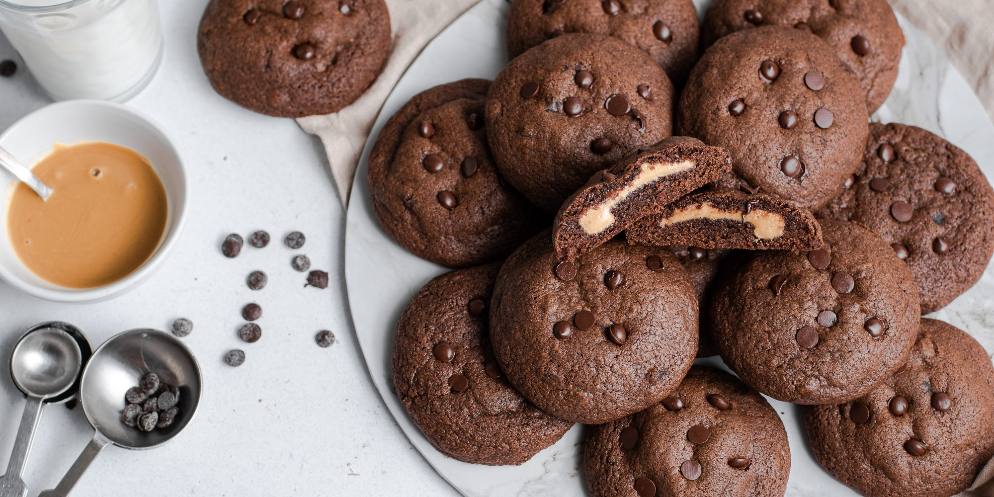 A batch of Chocolate & Peanut Butter Stuffed Cookies with a cookie sliced in half, showing the gooey insides.