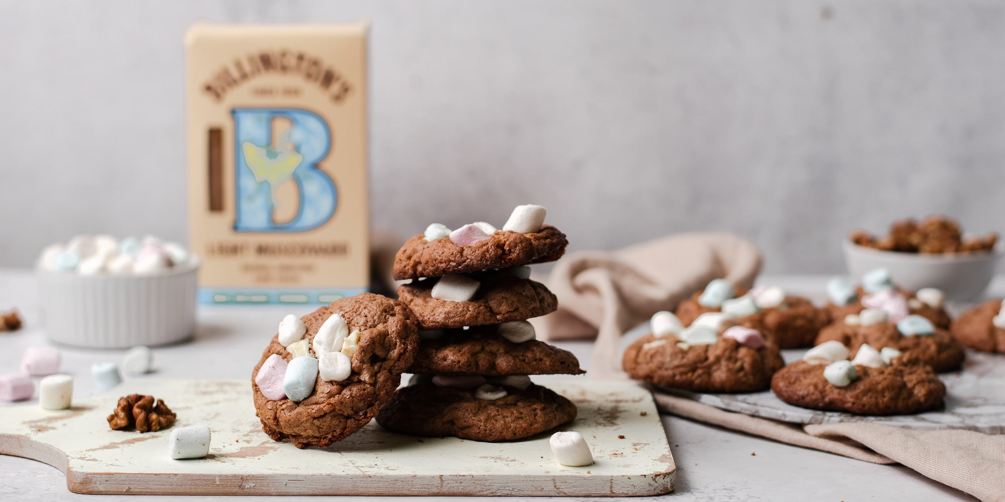 Rocky Road Cookies stacked on top of each other, on a serving board with a box of Billington's Light Muscovado in the background