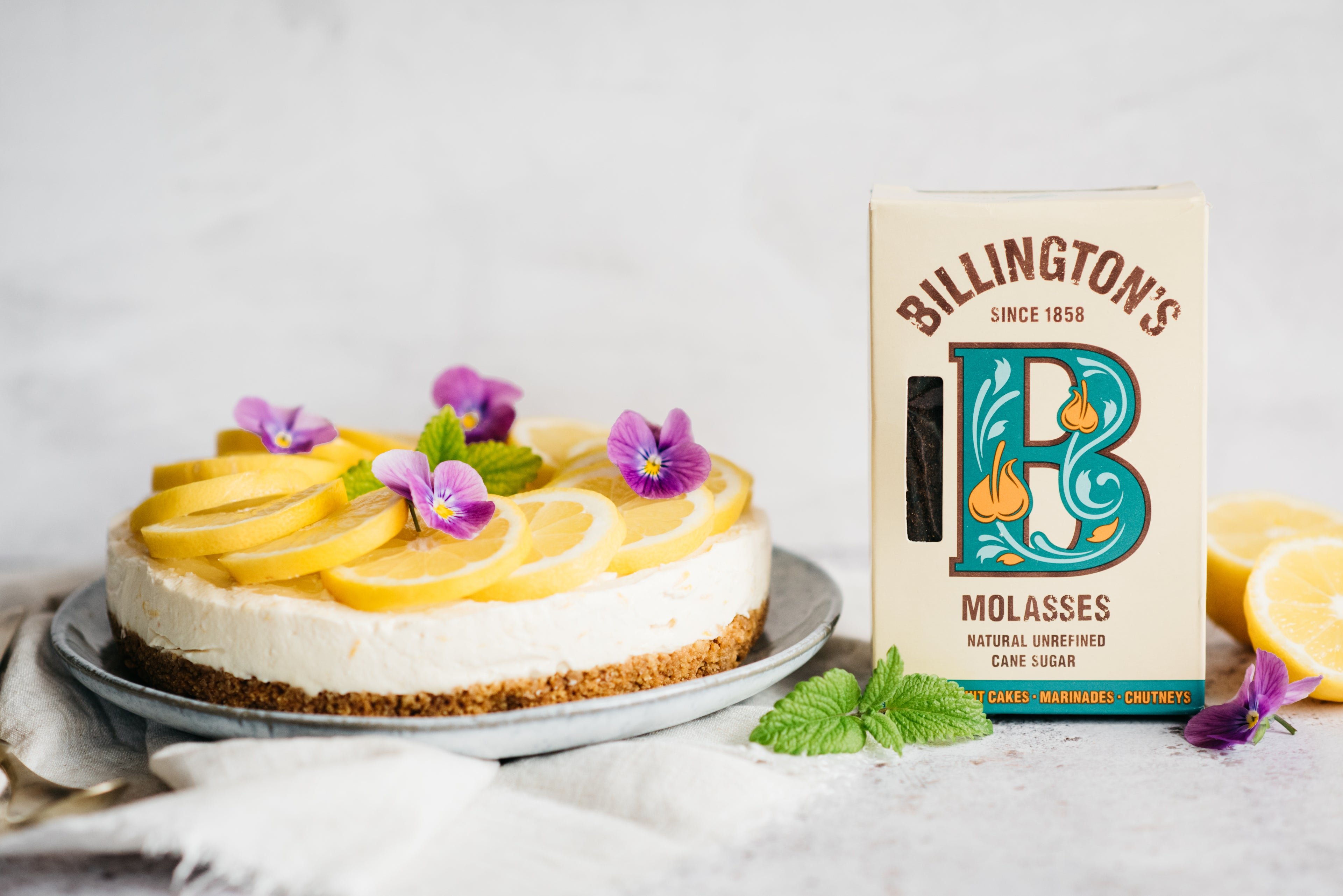 Lemon cheesecake with lemon and purple flower decoration and sugar pack
