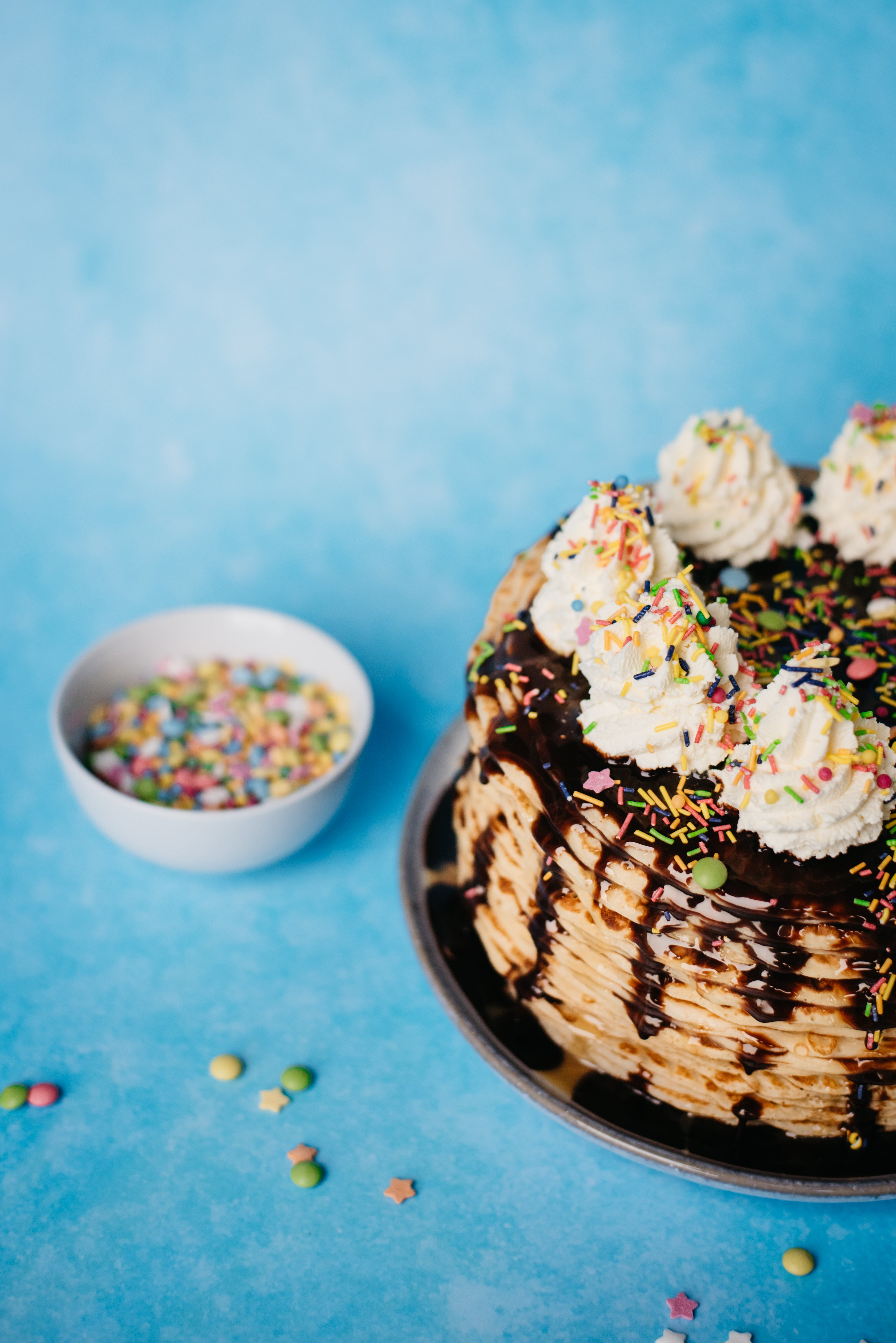 Crepe Cake with bowl of sprinkles at side