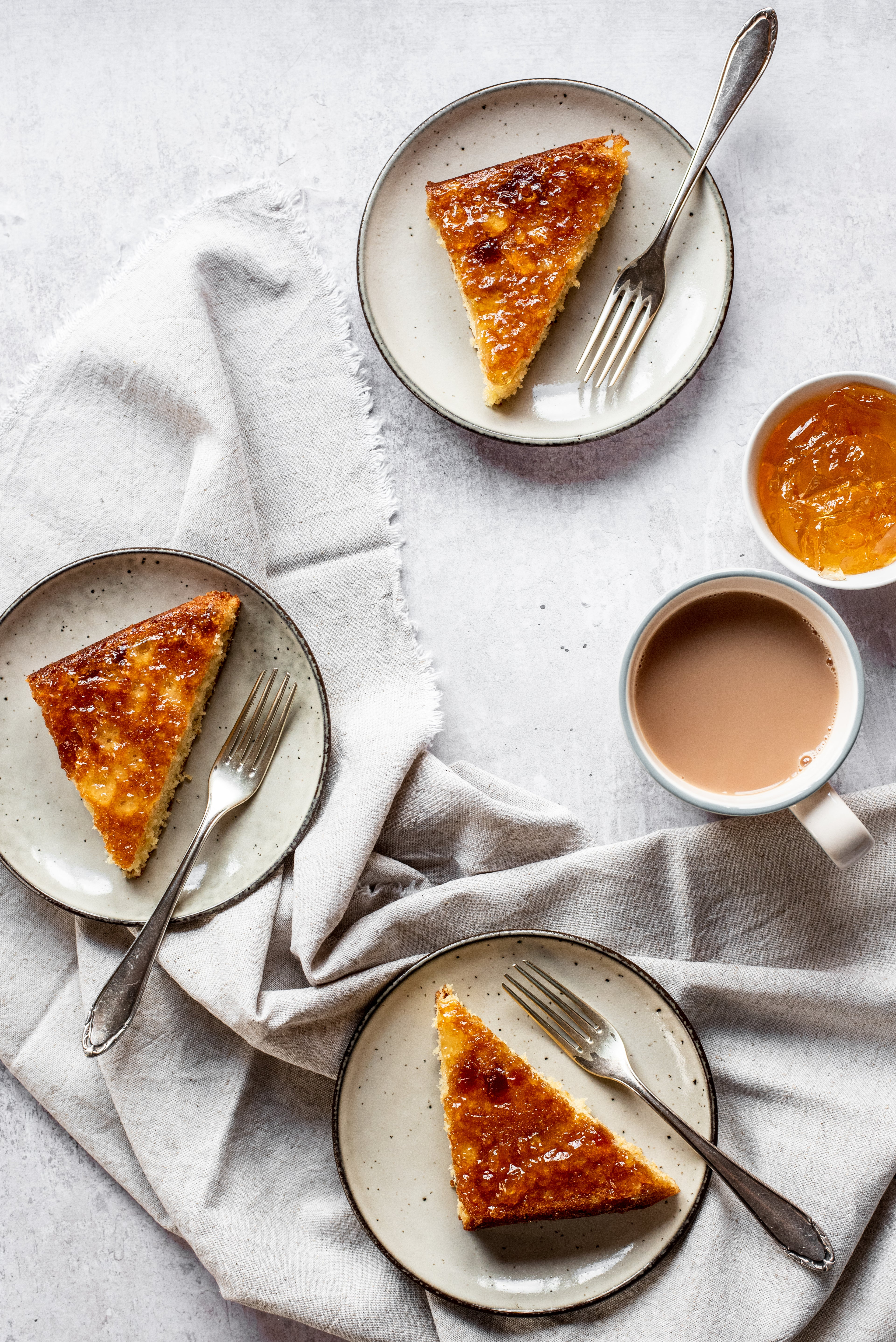 Flay lay of slices of Marmalade Traybake, on plates with forks, on top of linen next to a cup of tea and a bowl of marmalade