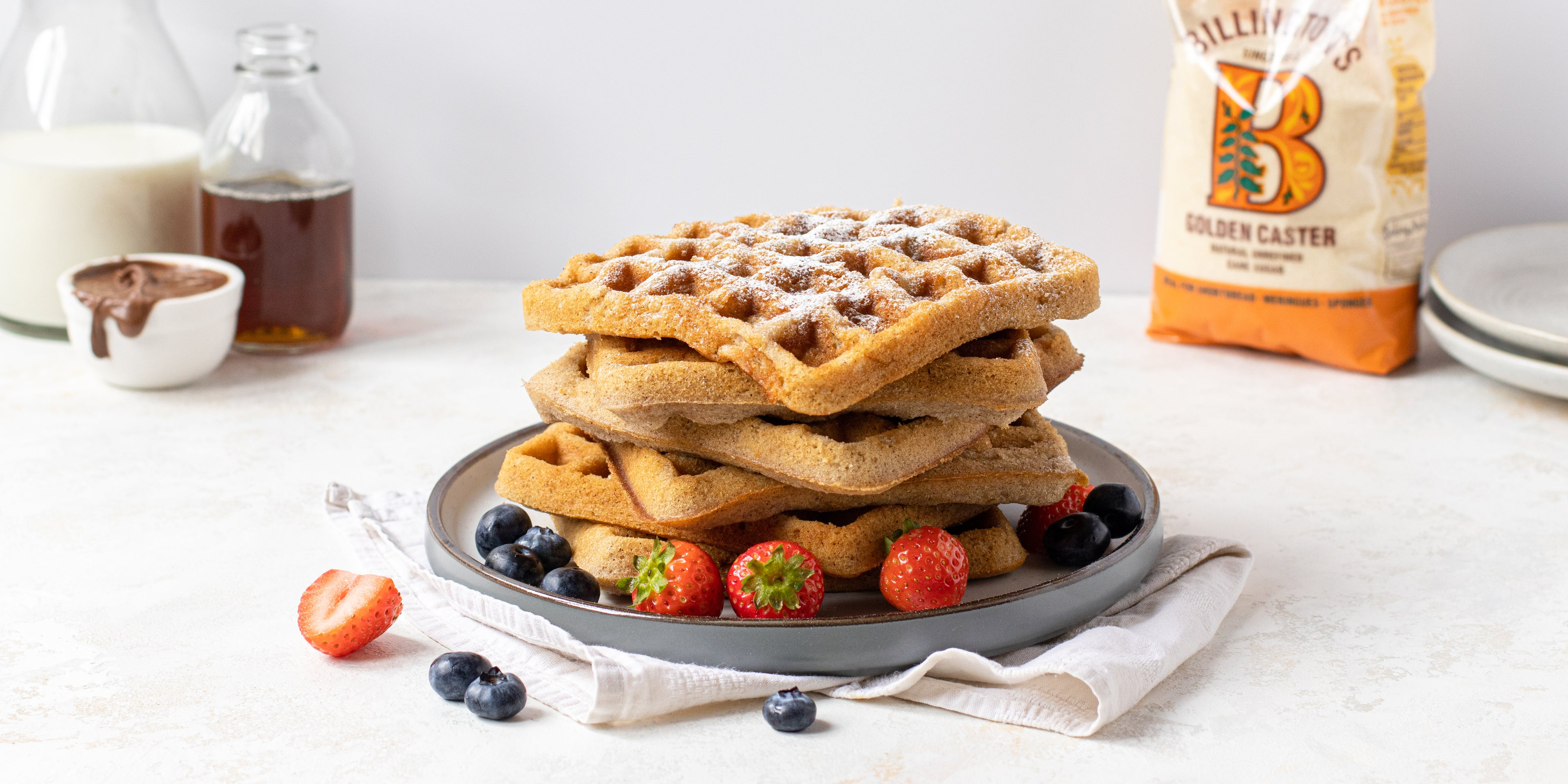Close up of a stack of fresh Waffles dusted with icing sugar and berries, with a bag of Billington's Golden Caster sugar in the background