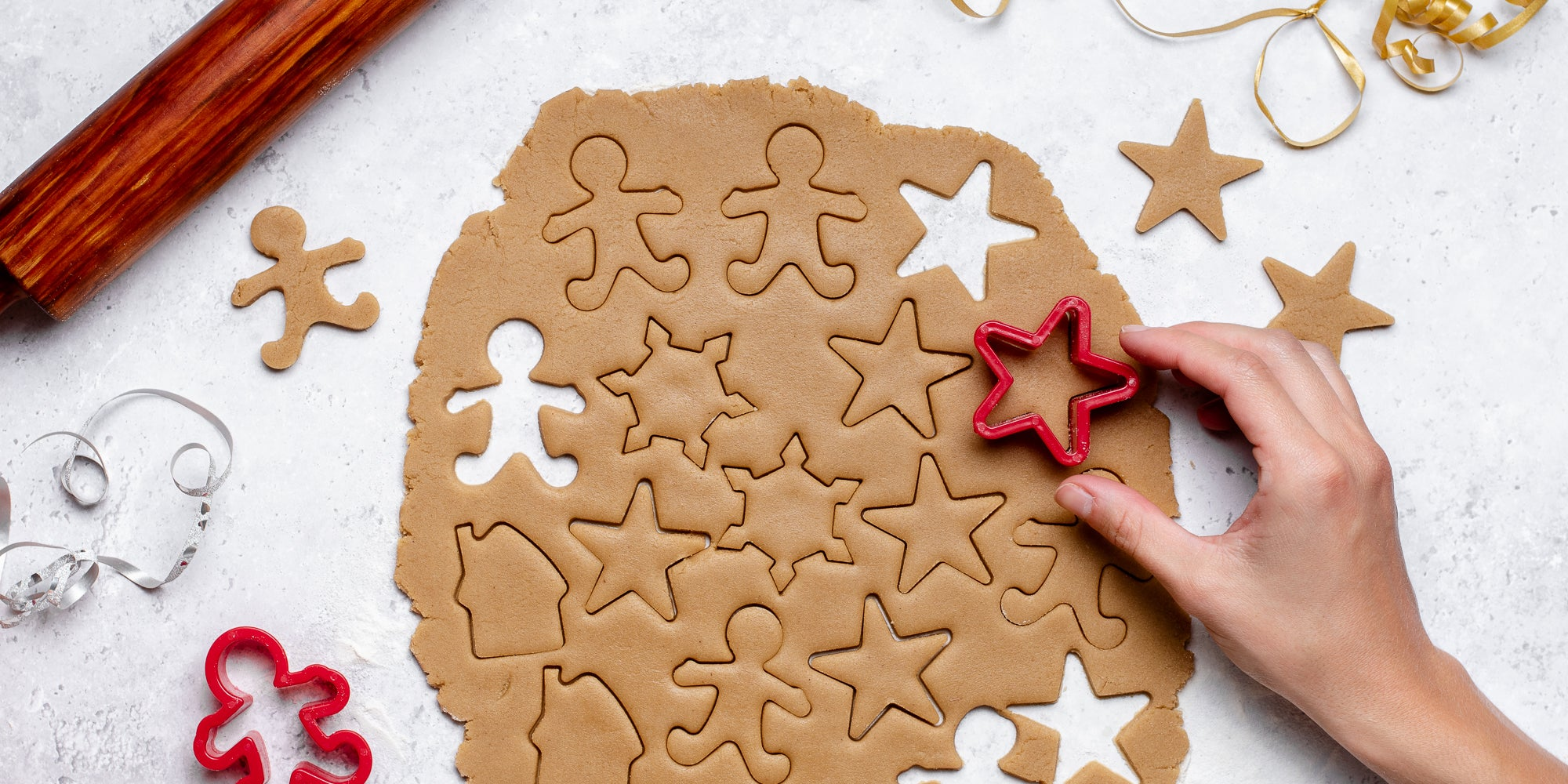 Top view of rolled out Gingerbread Dough with a hand cutting shapes out of it, next to a rolling pin and cut out gingerbread men and stars