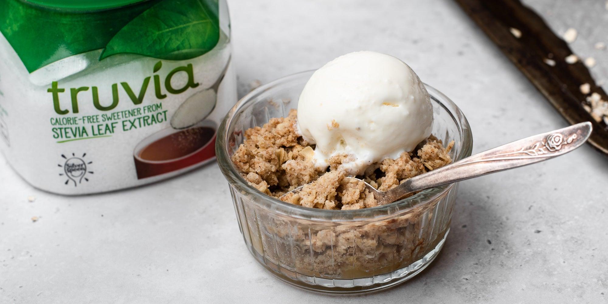 Close up of Mini Apple & Cinnamon Crumble in ramekin with ice cream and spoon. Sweetener pack