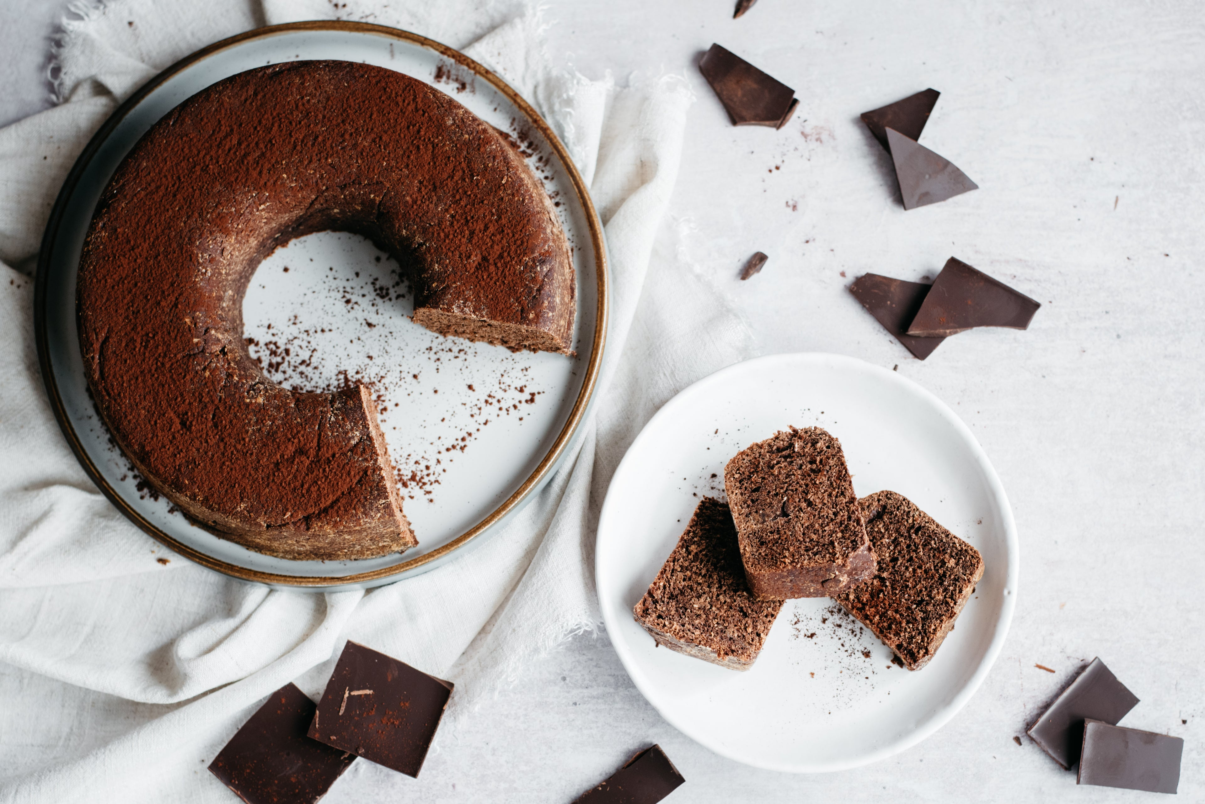 Top view of Chocolate Bread, with slices on a plate, dusted in cocoa powder.