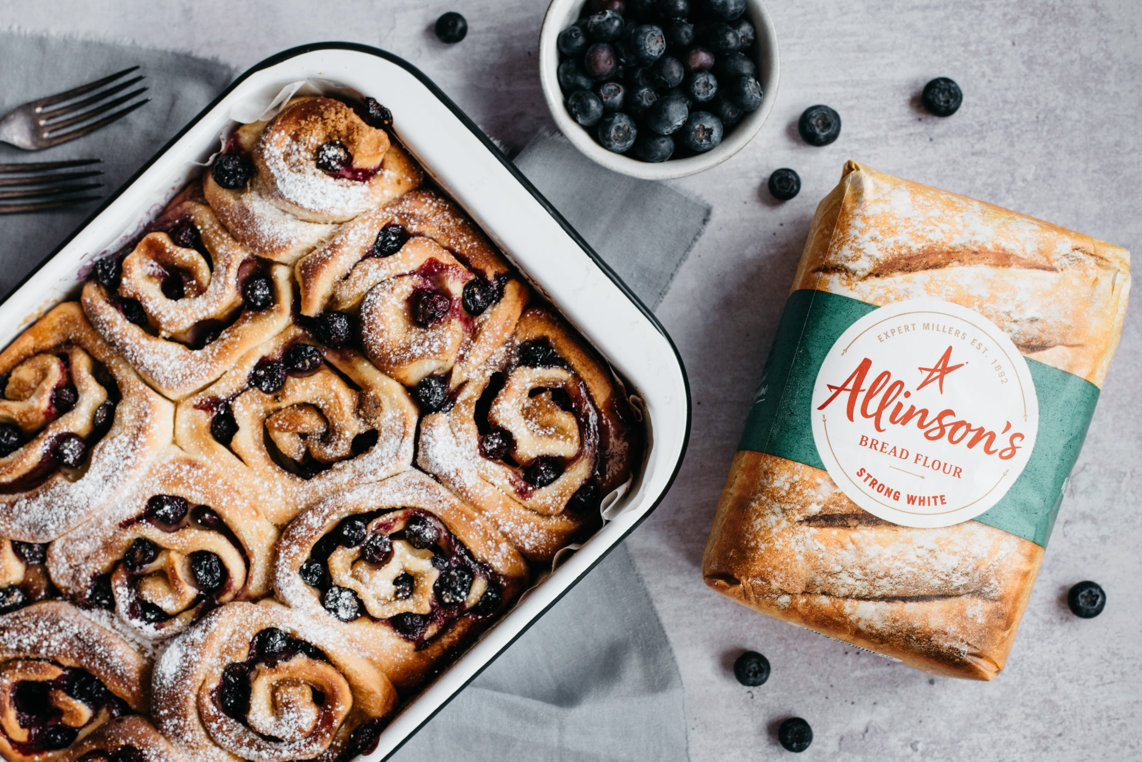Tray of blueberry and vanilla rolls, dusted with sugar, next to a bag of Allinson's Flour and bowl of blueberries