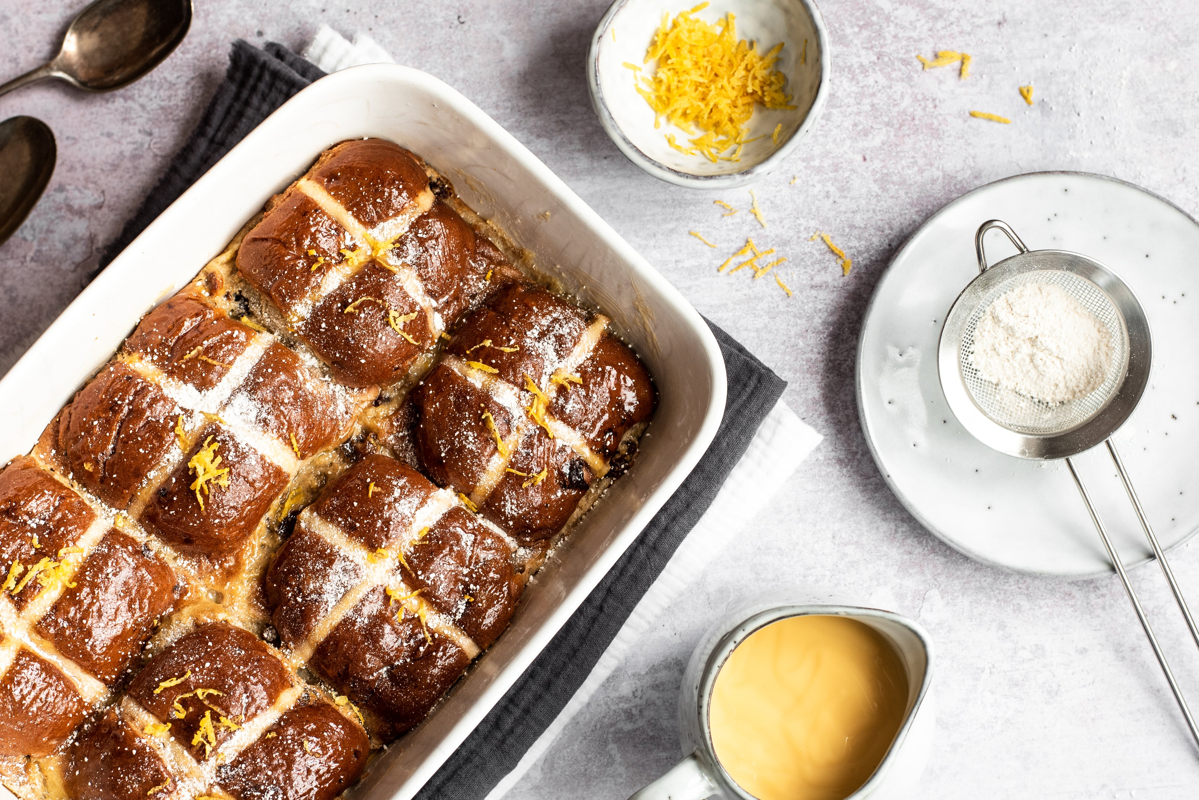 A tray-bake of Hot Cross Bun Bread Butter Puddings at an angle