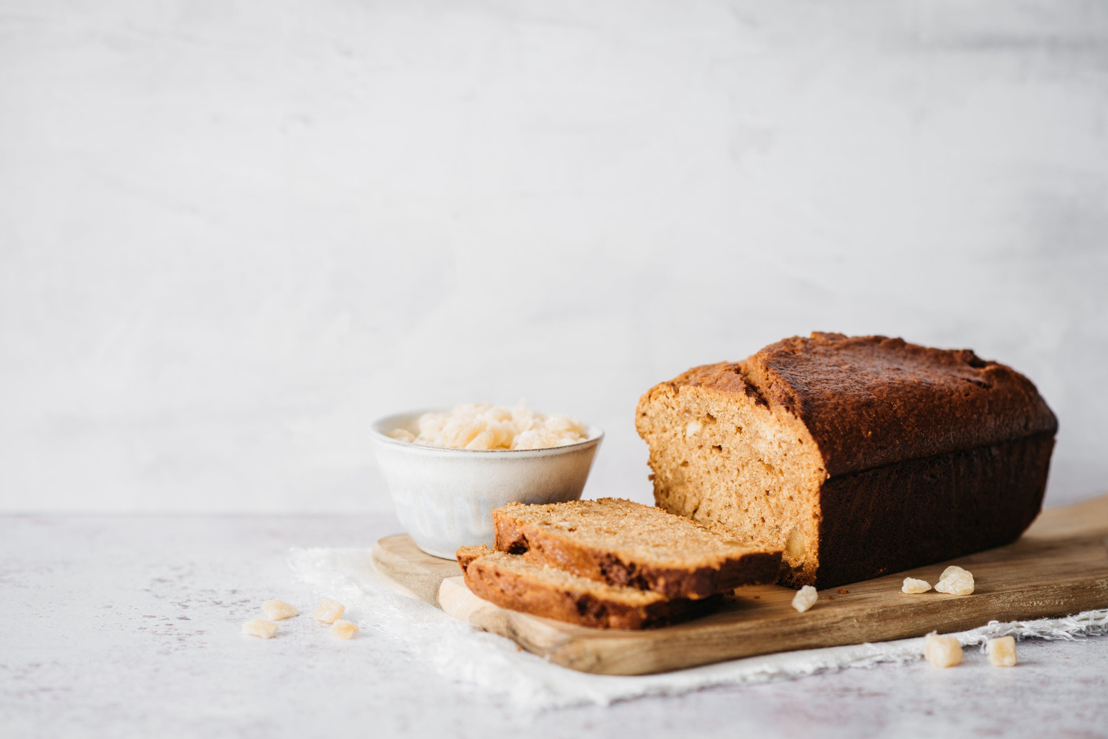 Gingerbread Loaf sliced on a wooden serving board, scattered with crystallised ginger