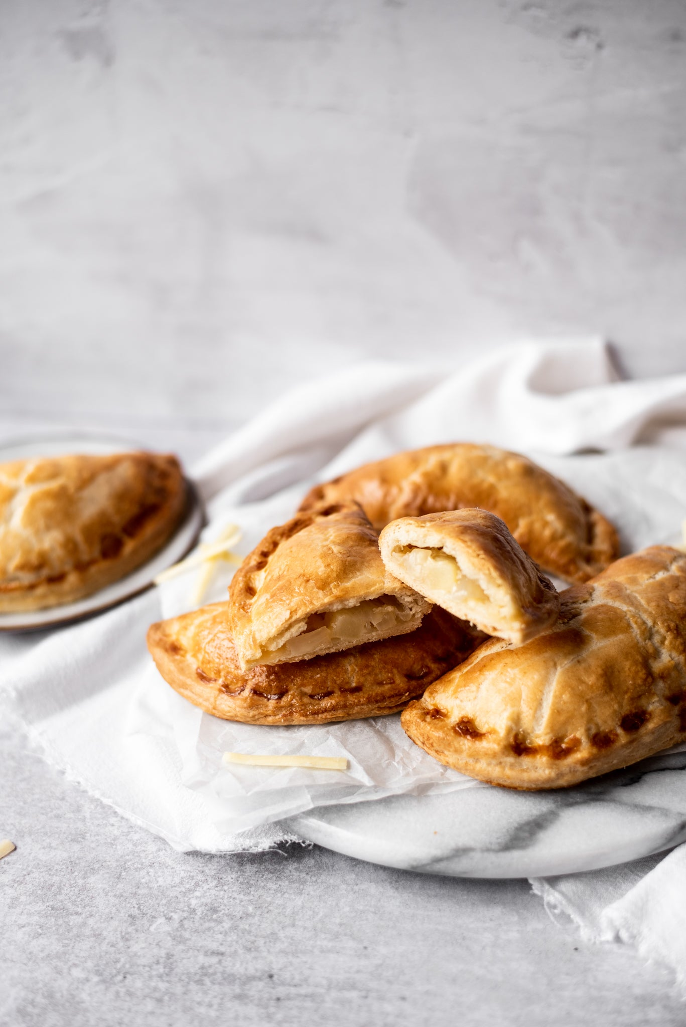 Pastie sliced open on top of pile of cheese and onion pasties