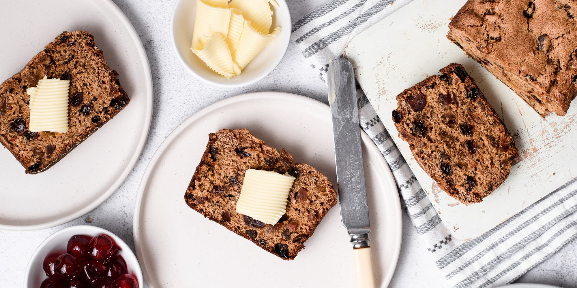 Irish Tea Brack sliced on plates with butter and preserves