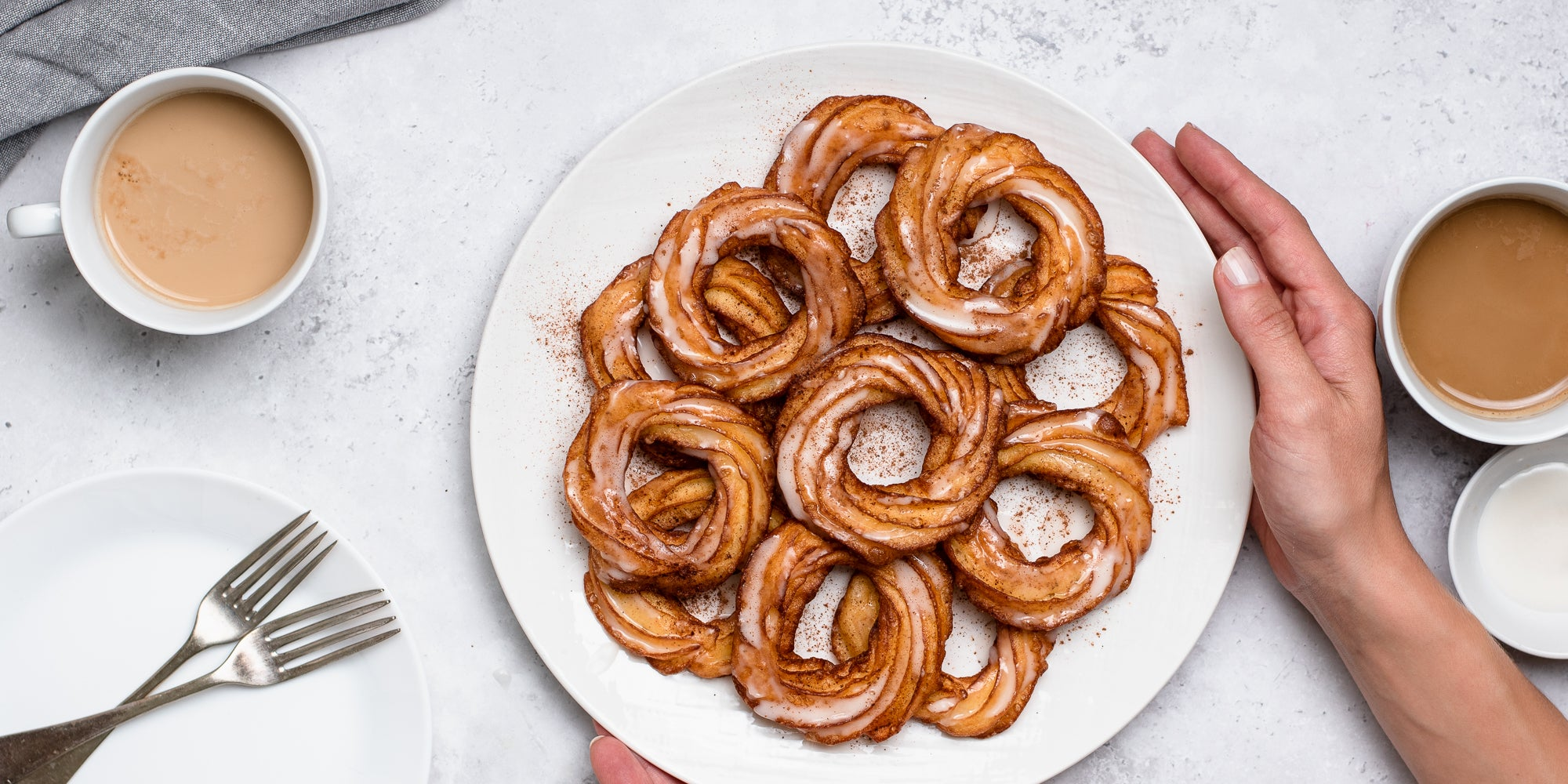 A plate of Apple Cider Crullers being held by hands. Dusted with cinnamon, next to cups of tea and cutlery