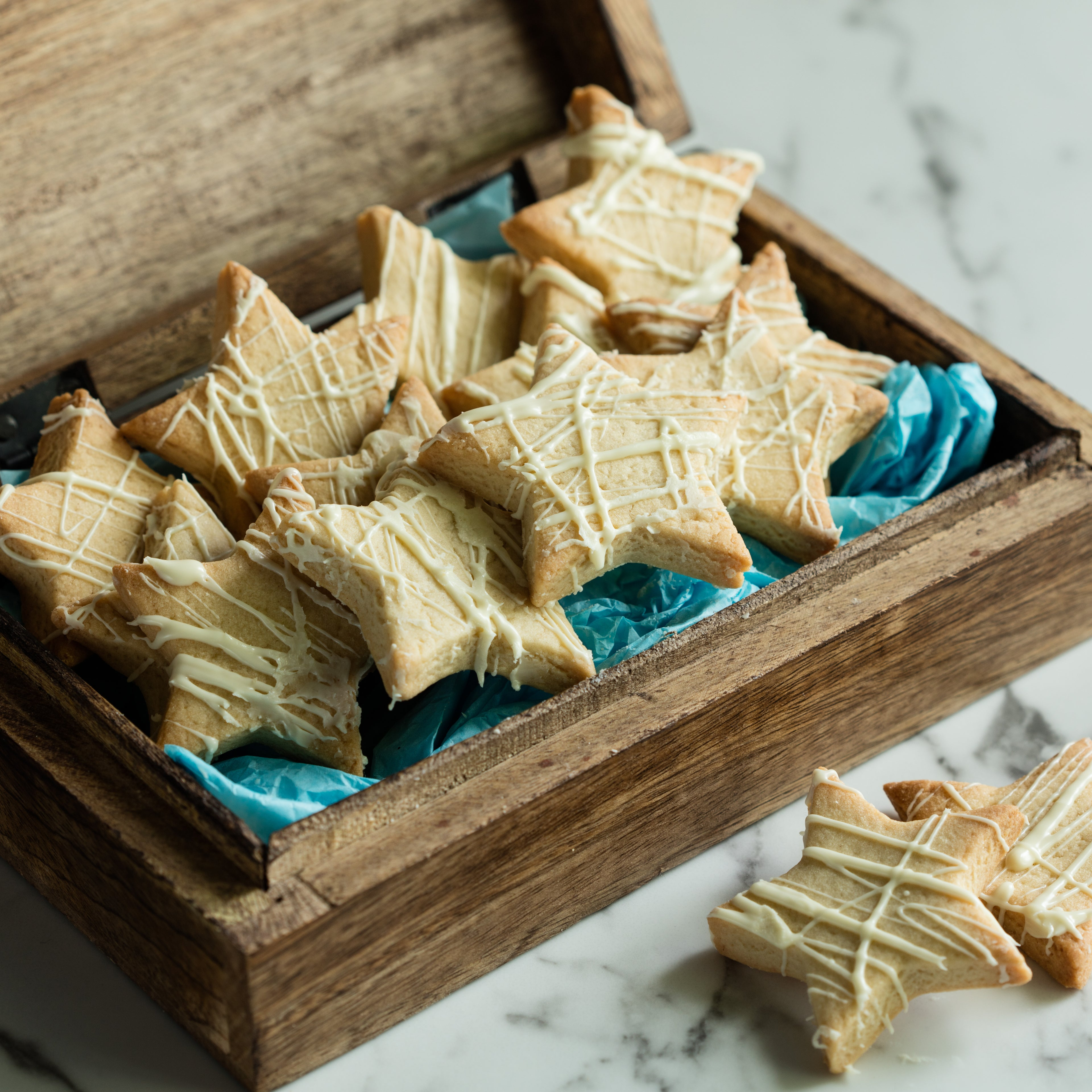 Star shaped biscuits inside a wooden box with blue tissue paper
