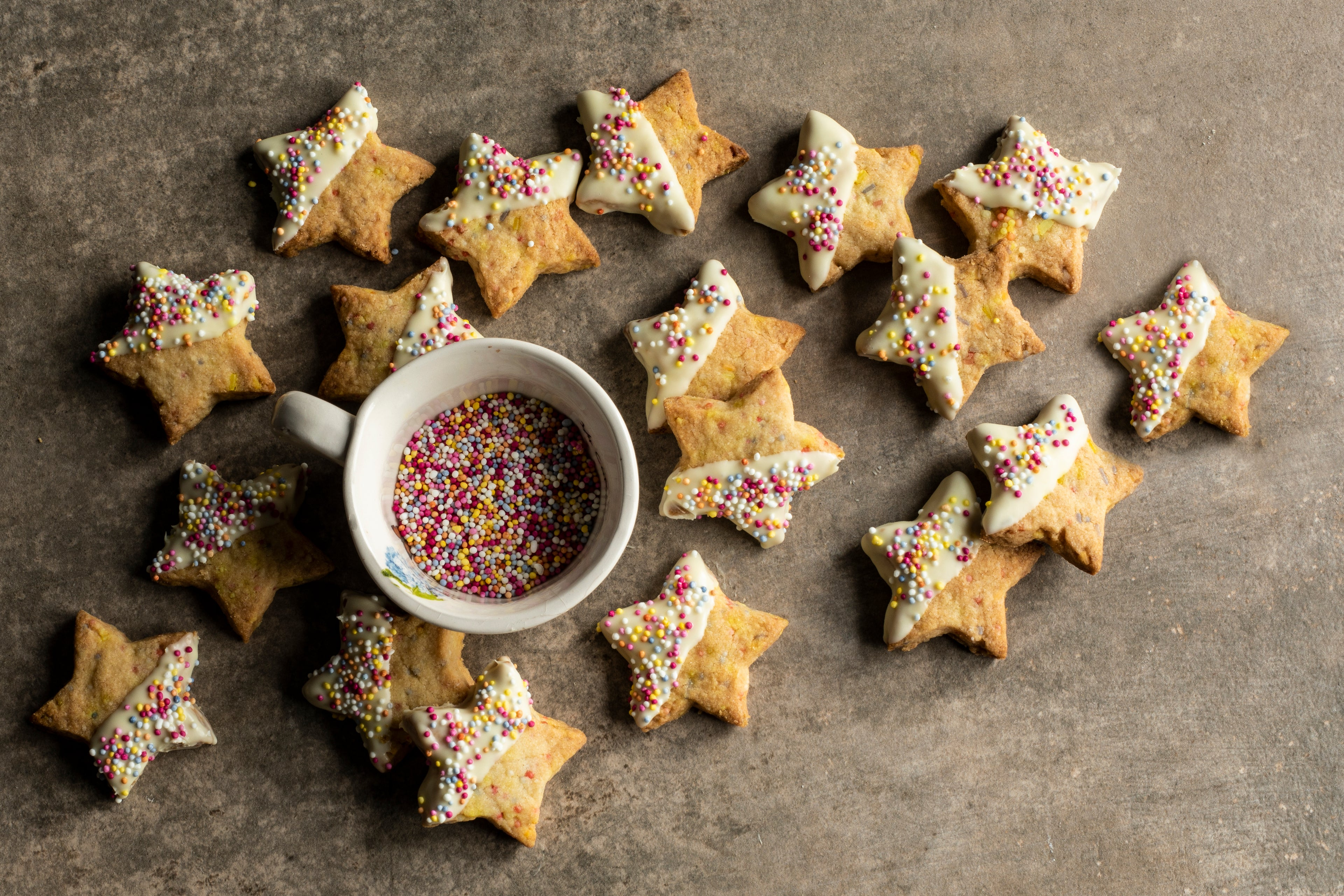 Star biscuits scattered around a small pot of sprinkles