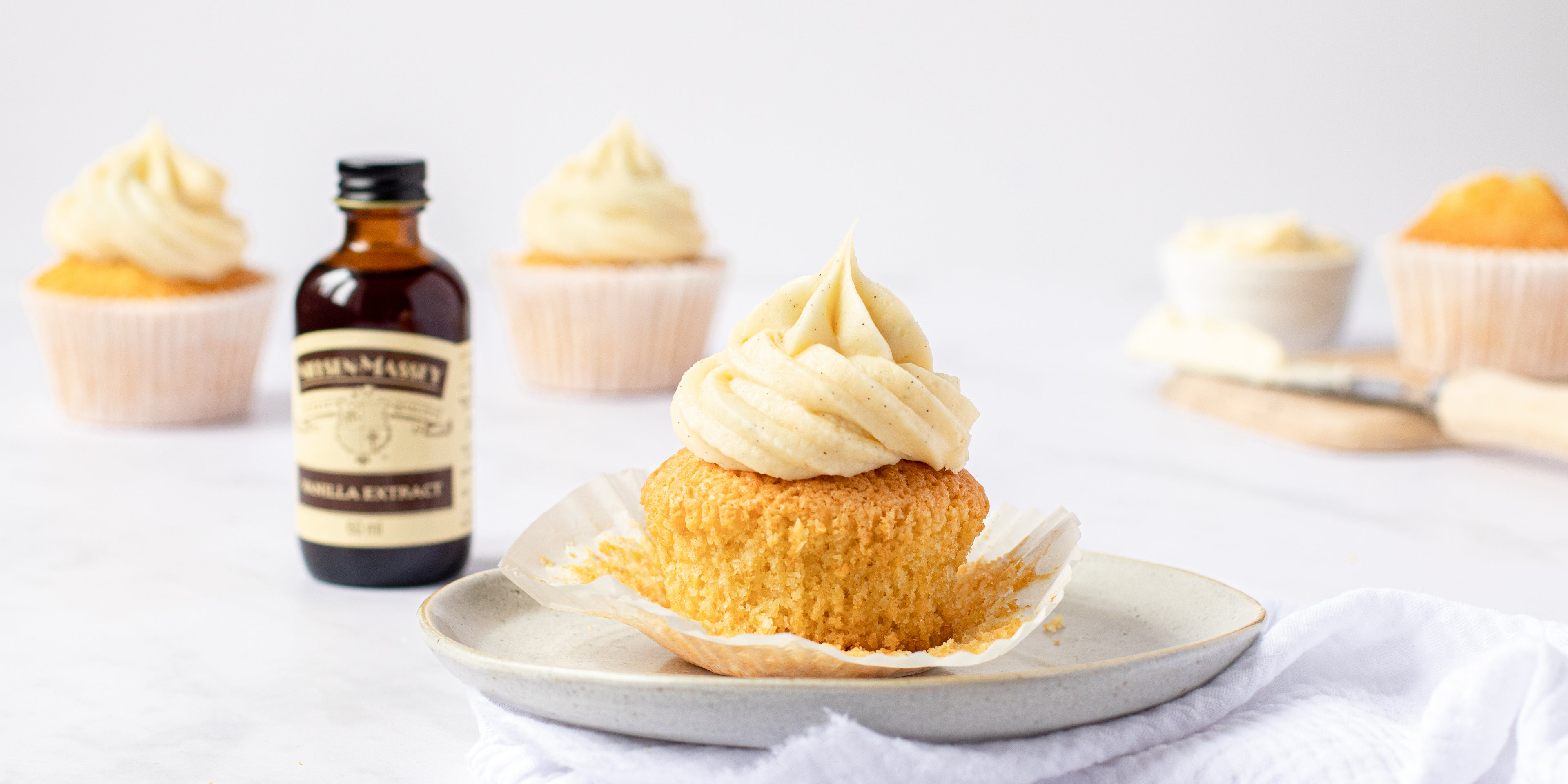 Vanilla cupcake topped with vanilla buttercream and a bottle of vanilla extract to the left