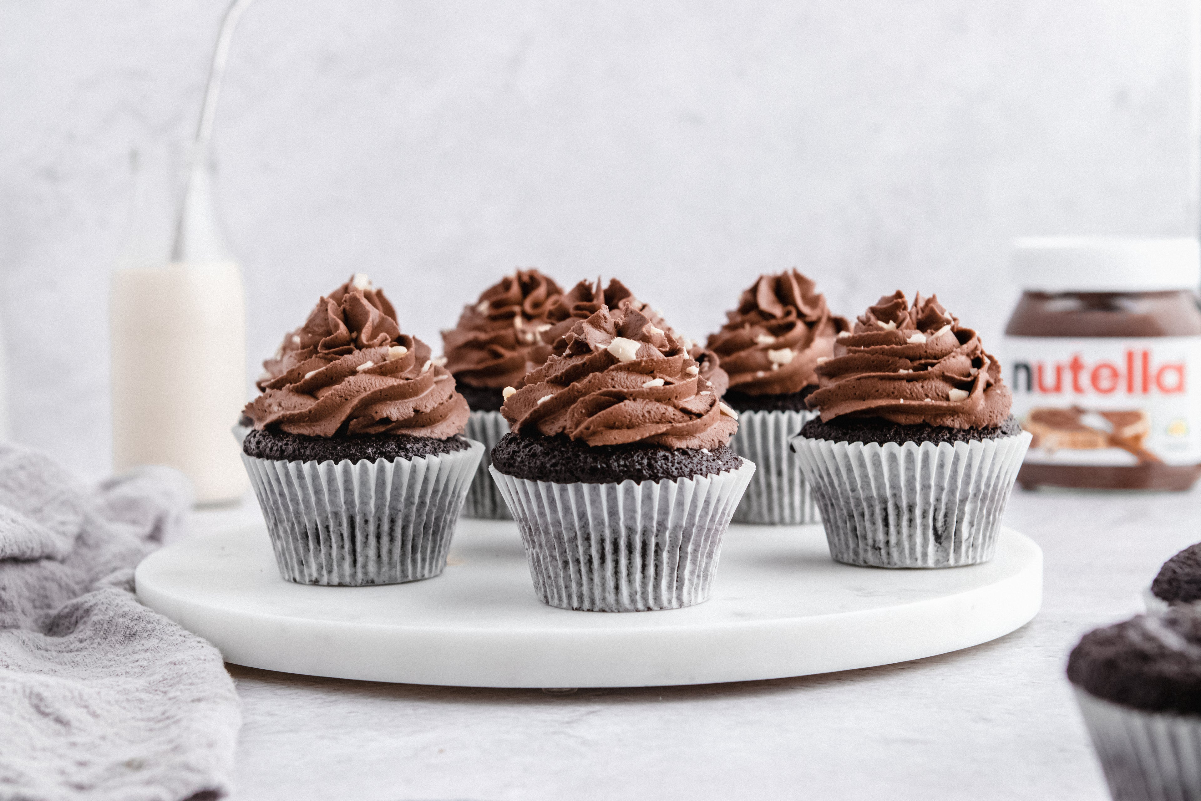 Nutella Cupcakes on a marble board, with a bottle of milk and jar of Nutella in the background