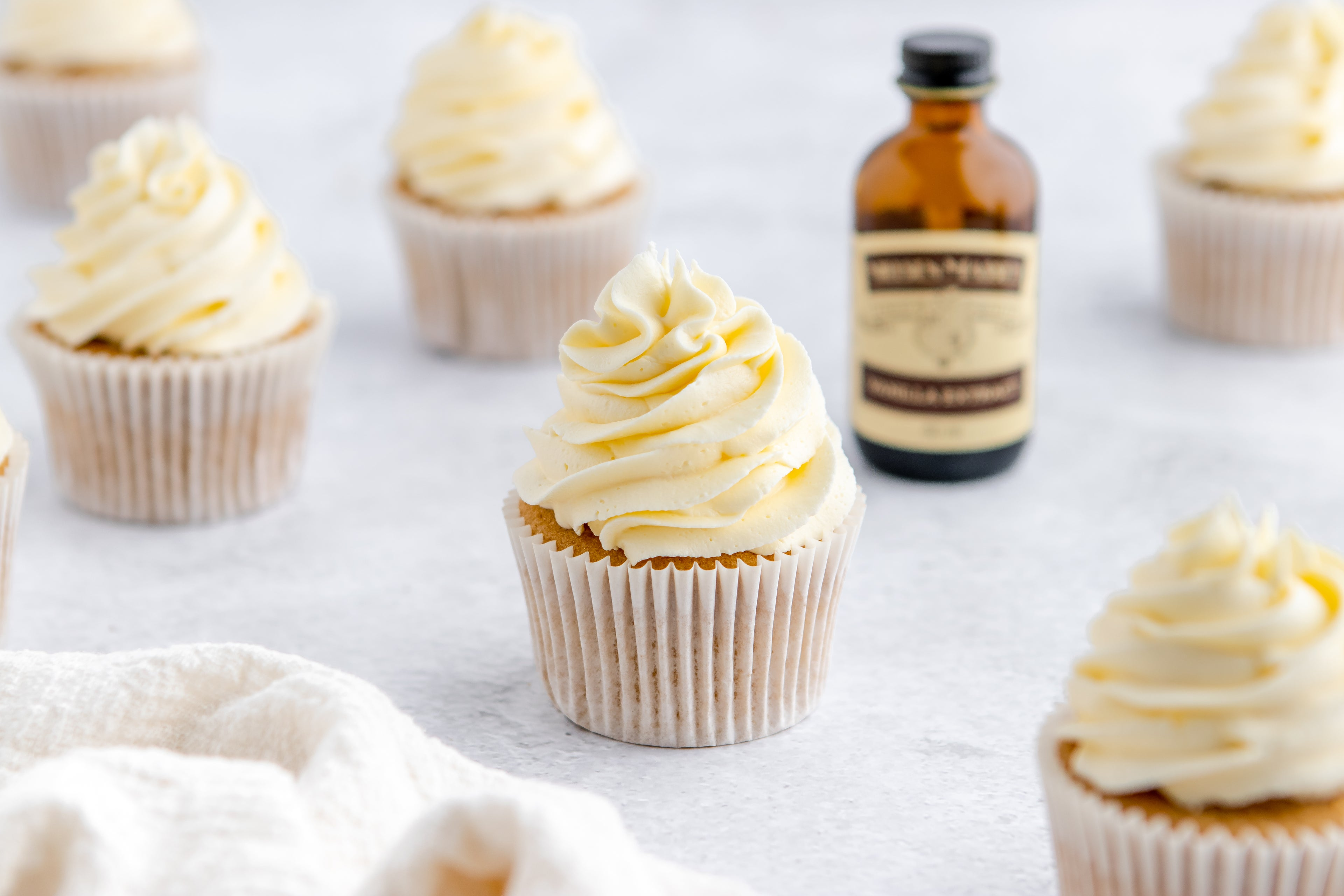 Close up of a Gluten Free Cupcake with a bottle of Neilsen-Massey vanilla extract in the background