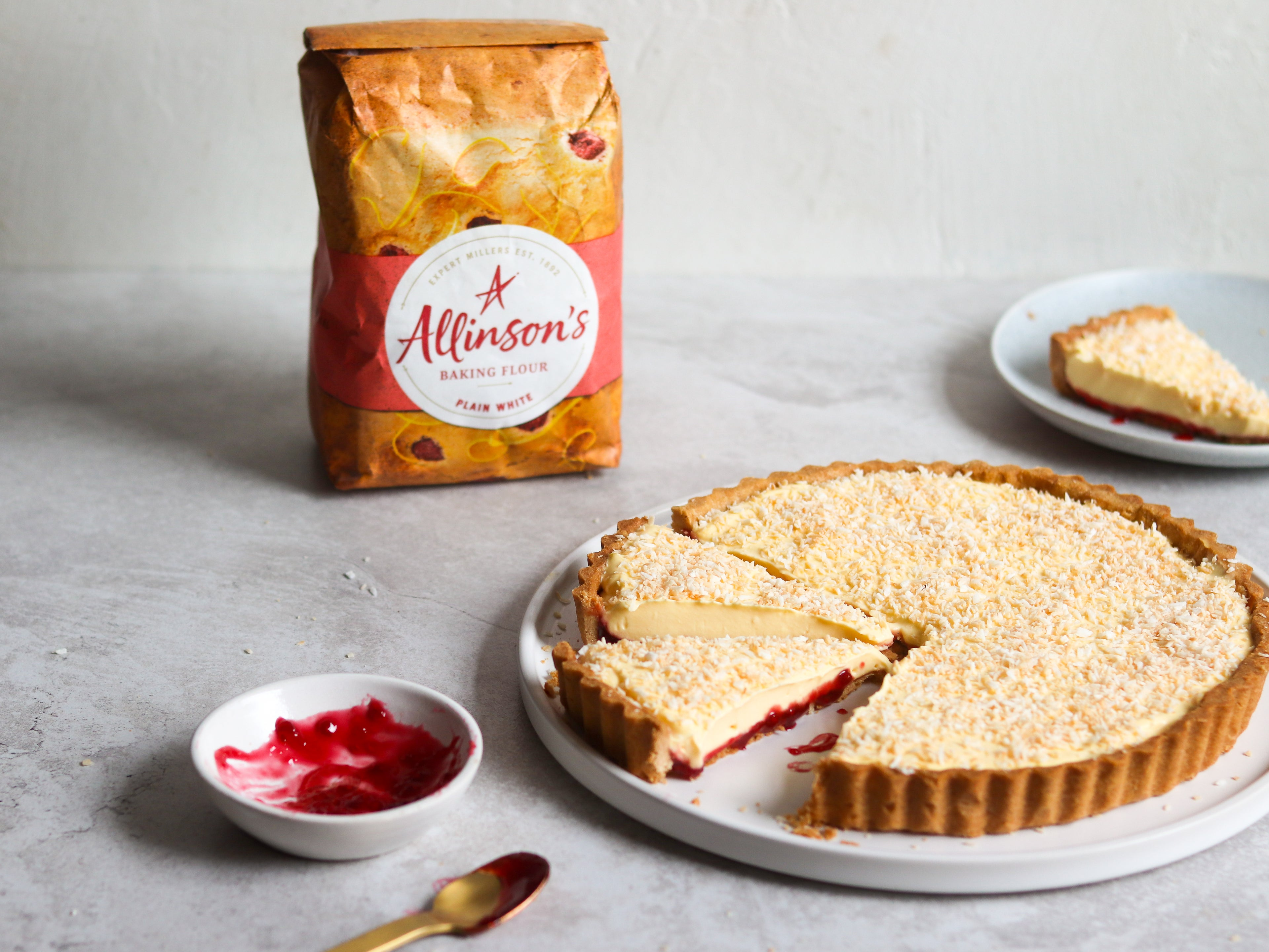 Manchester Tart with slice cut out of it, next to a bowl of jam and a spoon. Bag of Allinson's Plain Flour in background