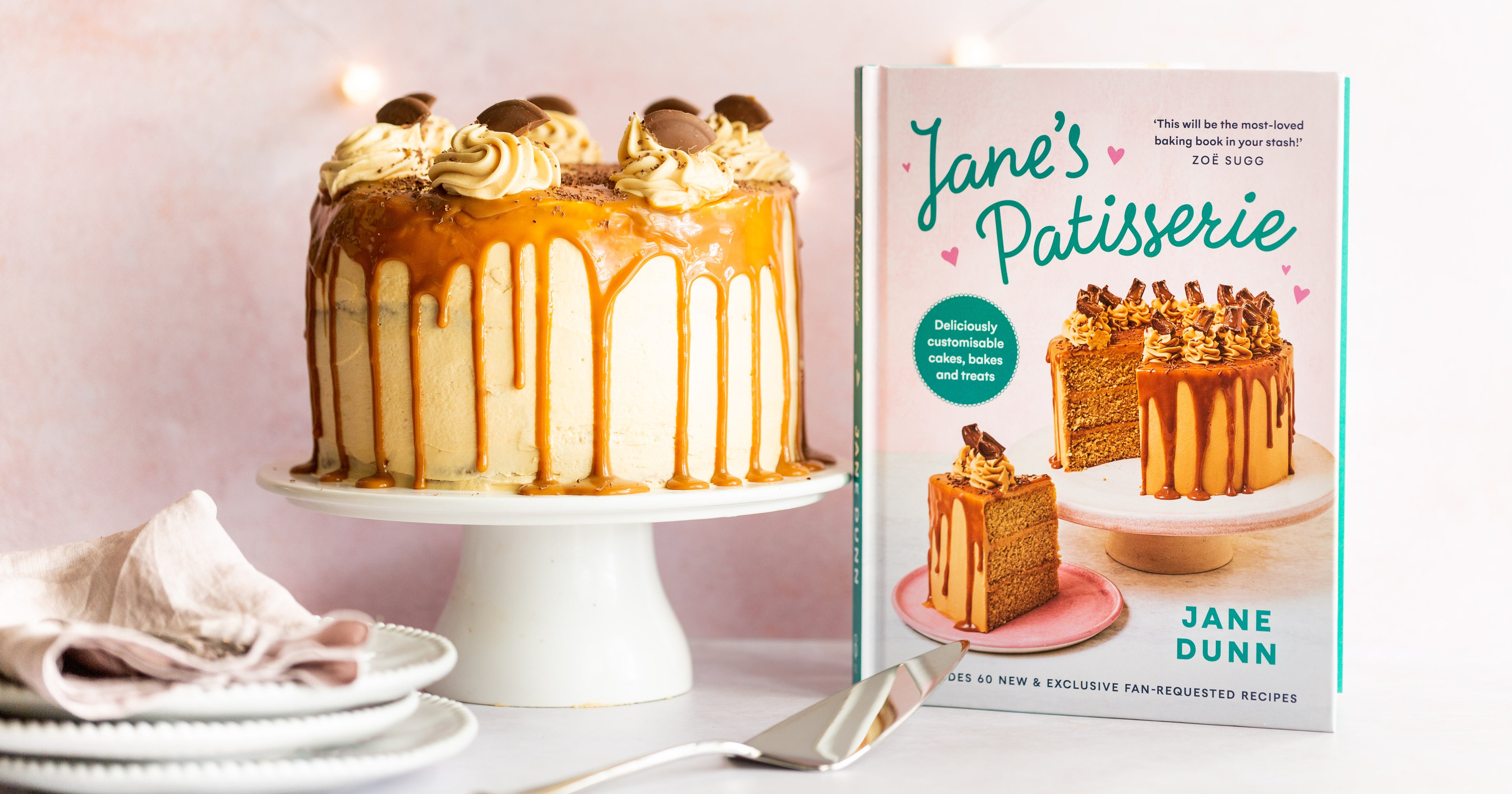 Cake on cake stand with caramel dripping down the side. A stack of white plates. A cake slice and a recipe book