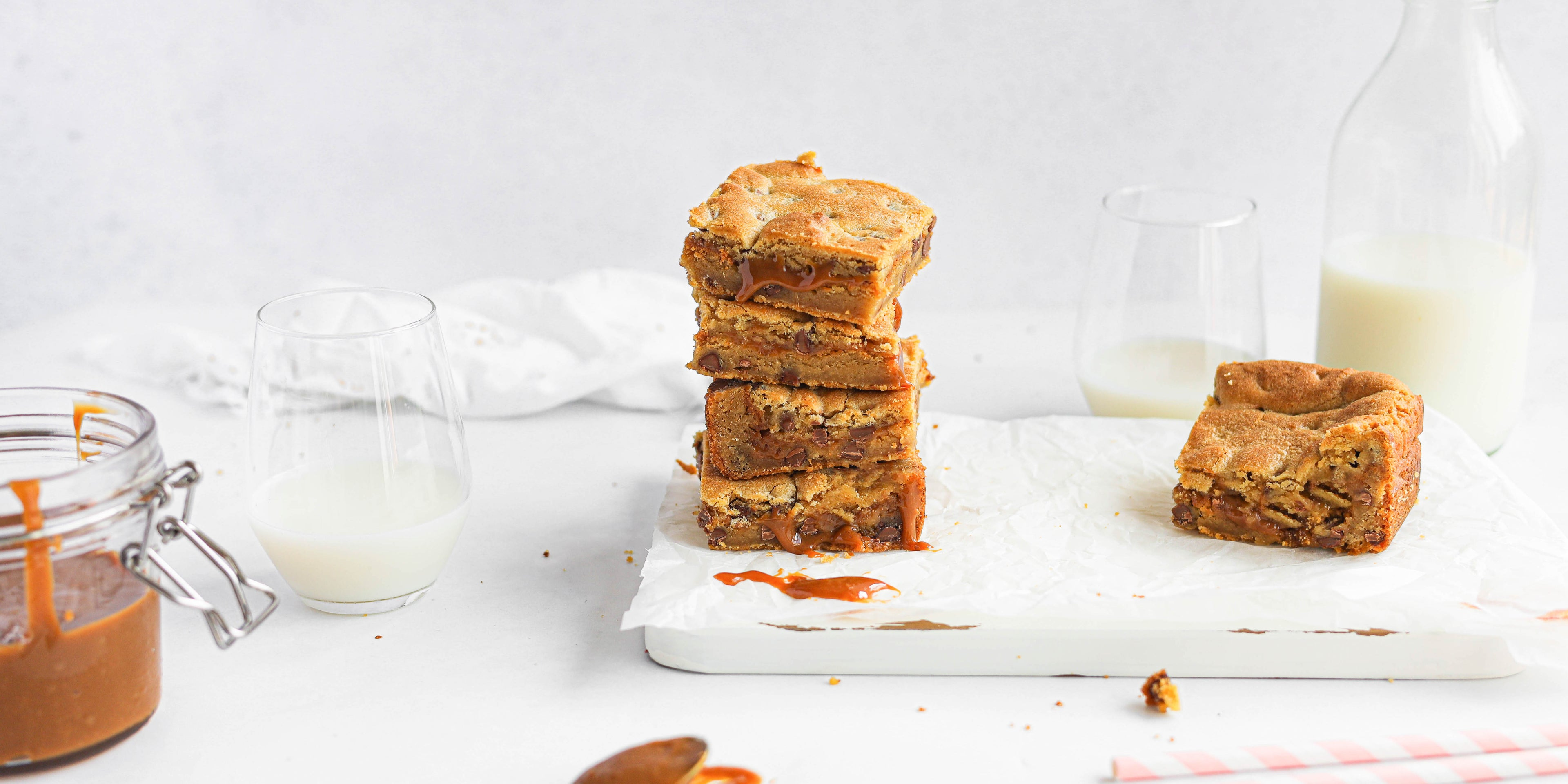 Stack of Salted Caramel Cookie Traybake on baking paper on a marble serving board, next to a jar of caramel and a half full glass of milk