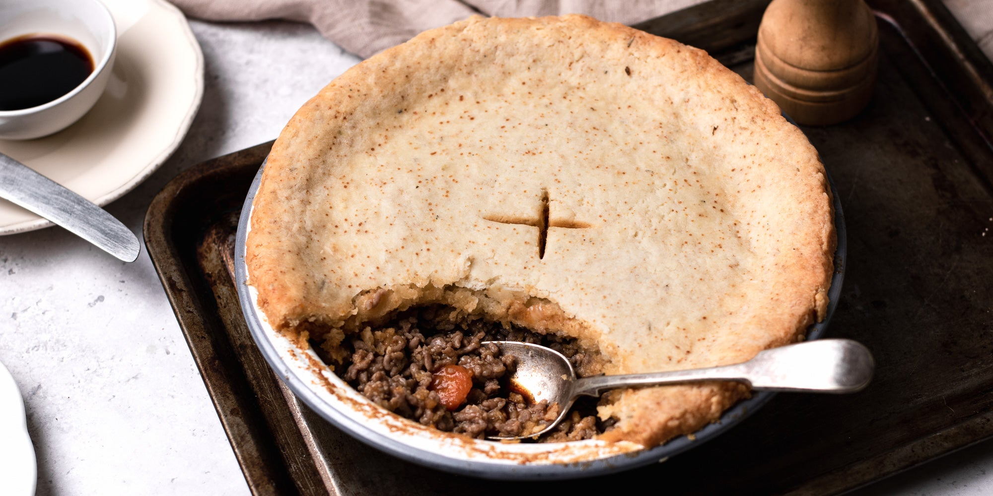 Close up of Suet Crusted Beef & Onion Pie, with a spoon inside the filling. Served on a baking tray