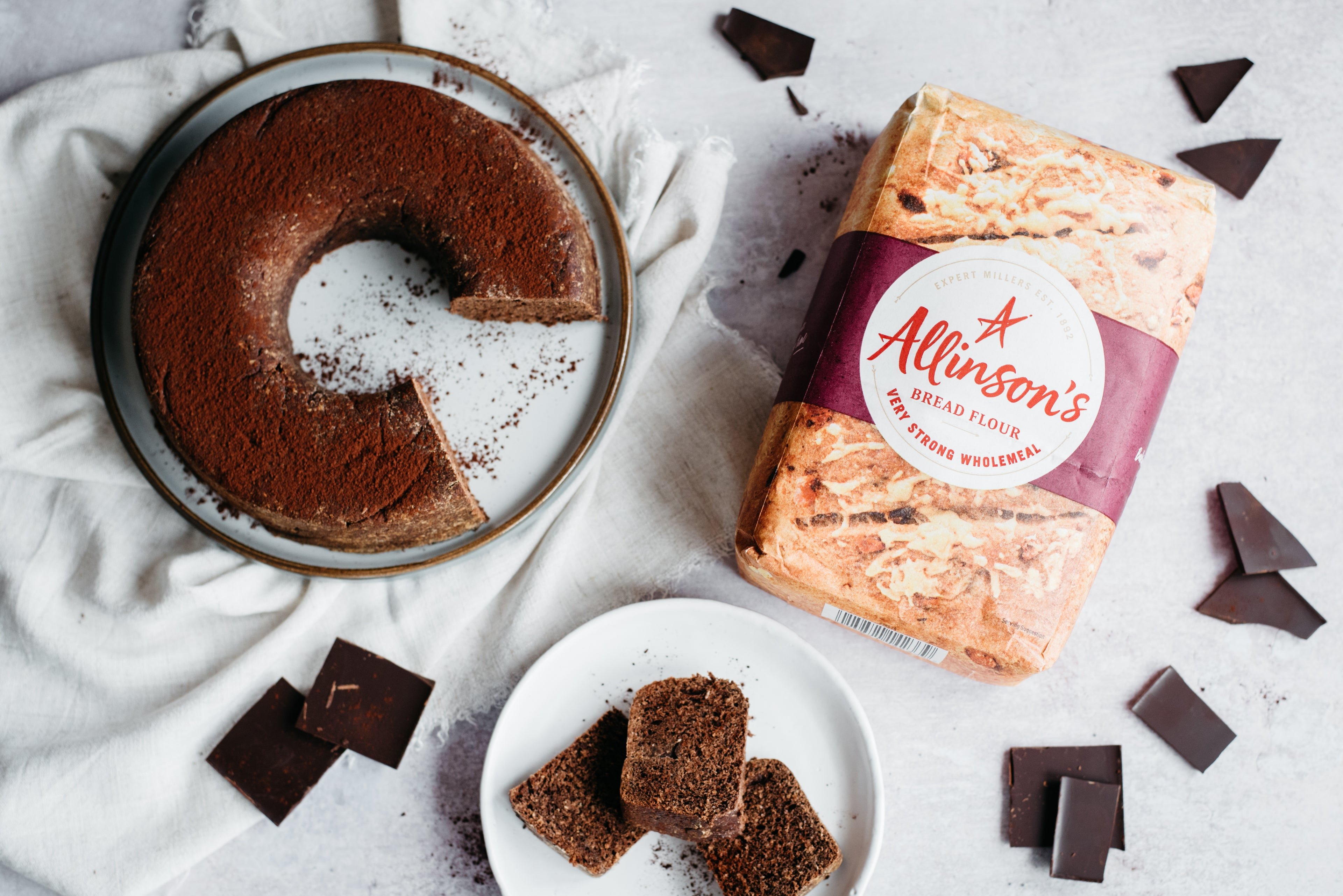 Top view of Chocolate Bread on a plate, with slices cut out and served on a plate, with dark chocolate pieces scattered around. Next to a bag of Allinson's very strong flour