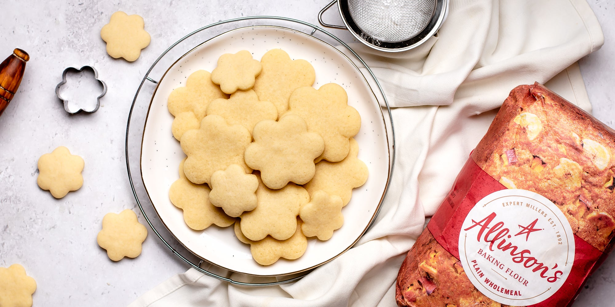 A plate of biscuits baked using the Basic Biscuit Dough recipe, next to a bag of Allinson's flour and biscuit cutters