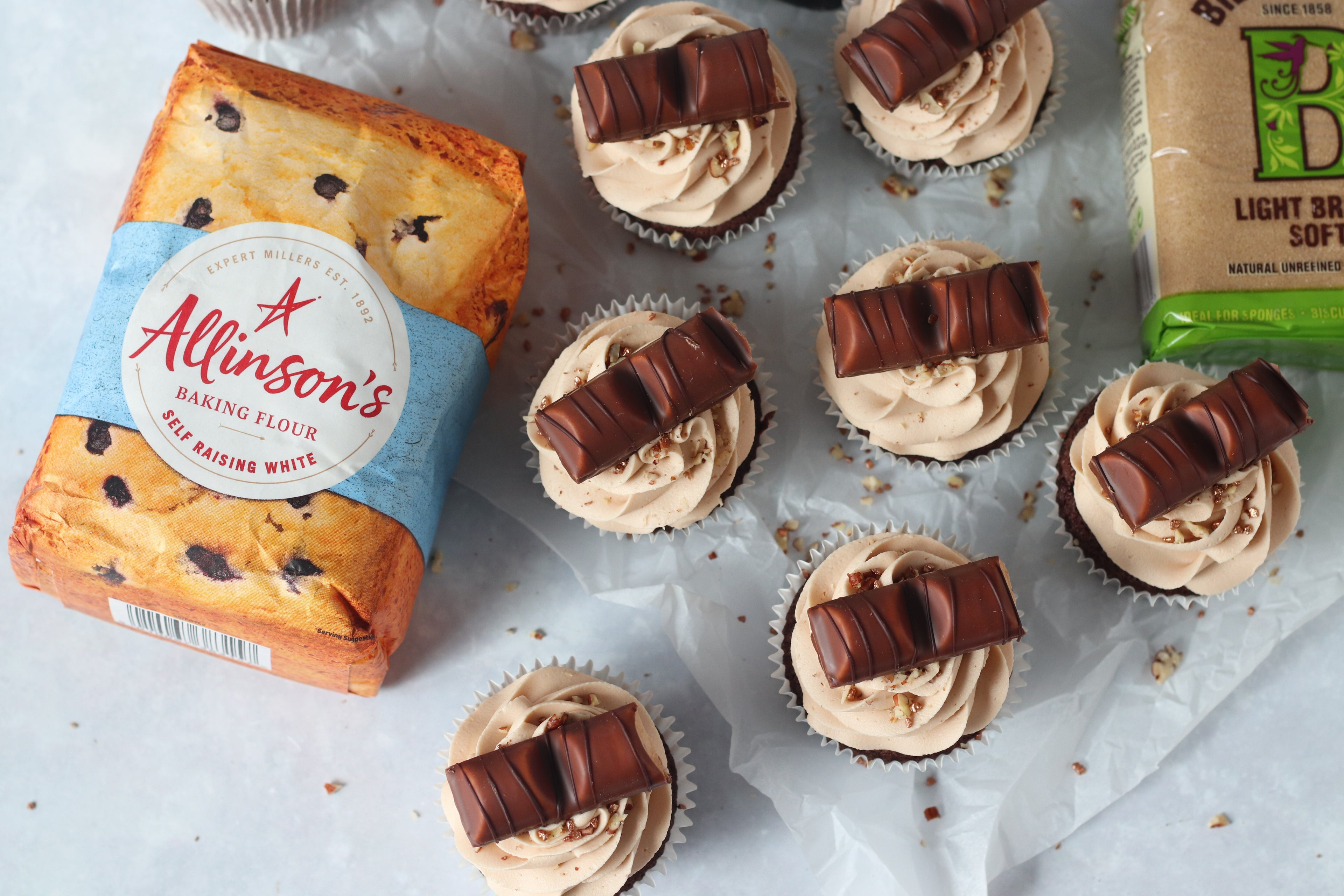 Overhead shot of 7 kinder bueno cupcakes with flour and sugar pack