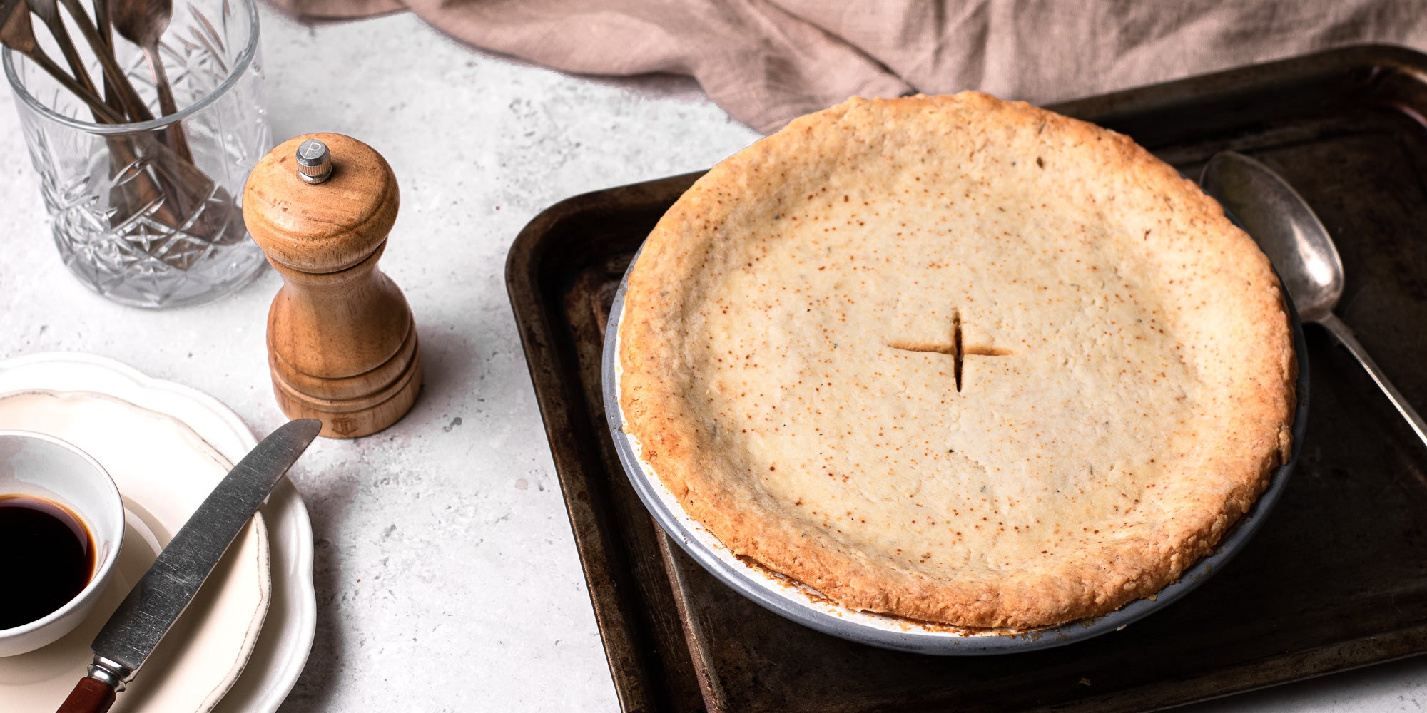 Suet Crusted Beef & Onion Pie on a baking tray, next to a pepper mill and a set of plates with a knife ready to serve