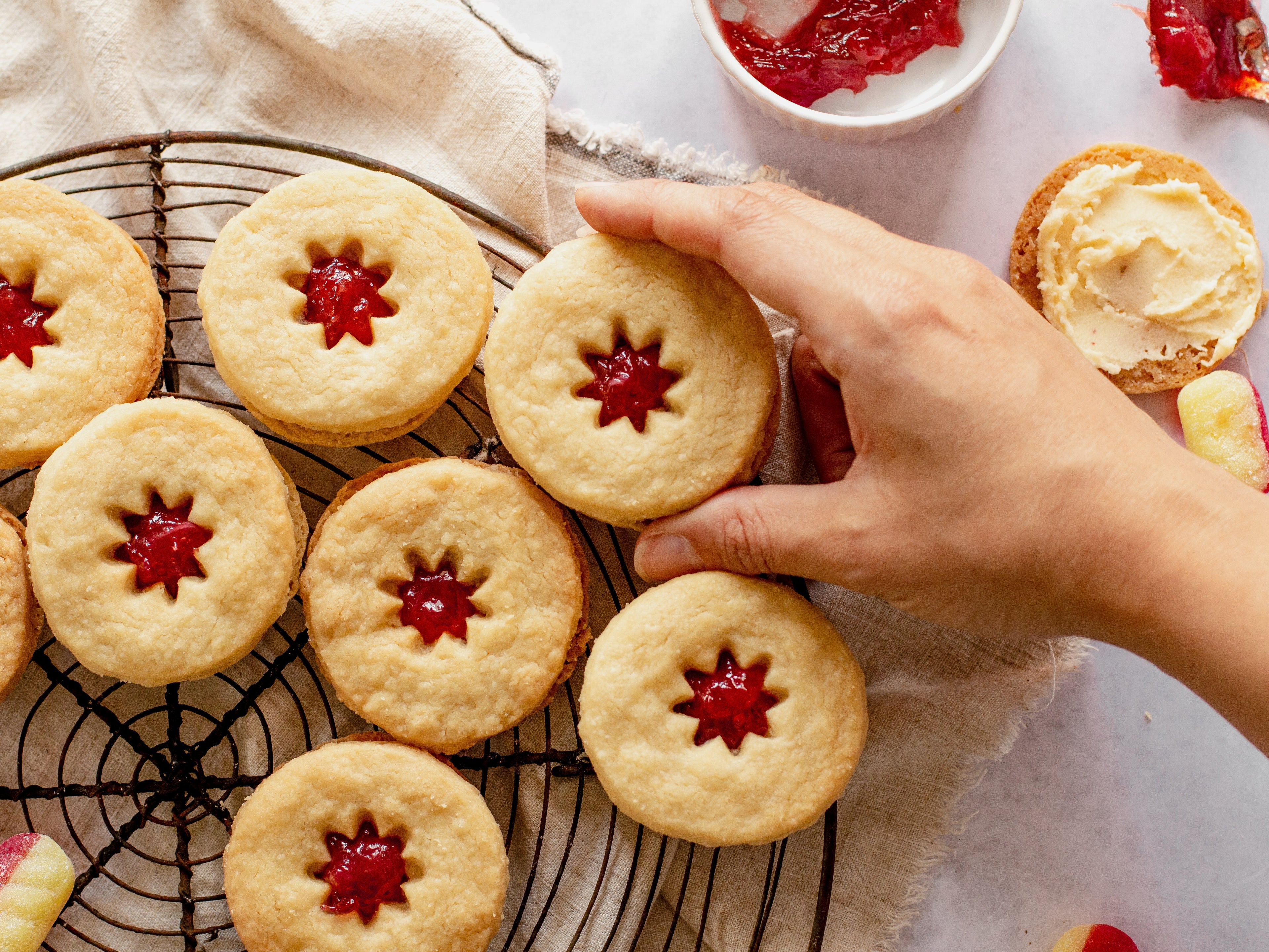 Jammy dodgers on wire cooling rack with hand