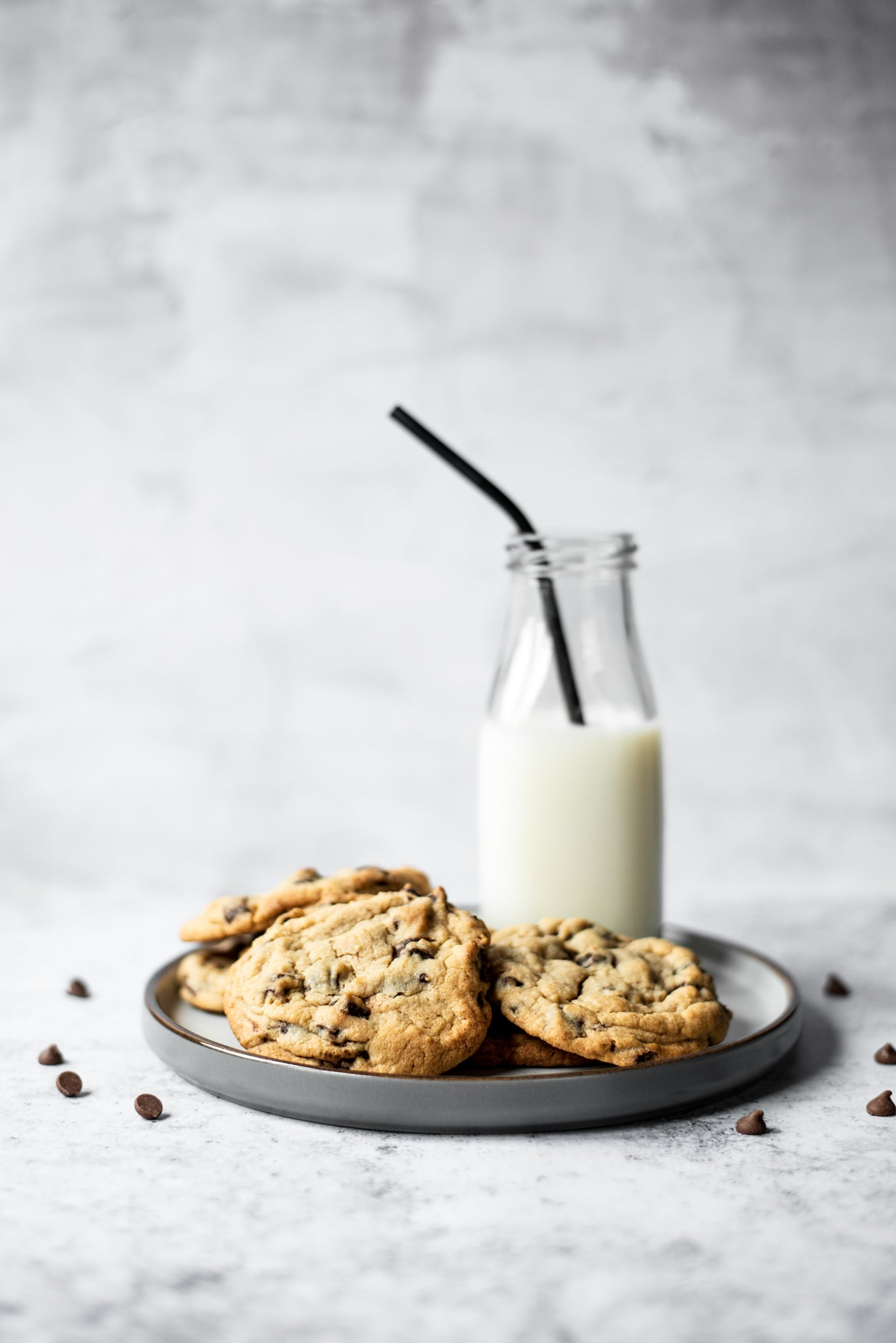 A plate of copycat millies cookies and a glass of milk in a bottle with a straw
