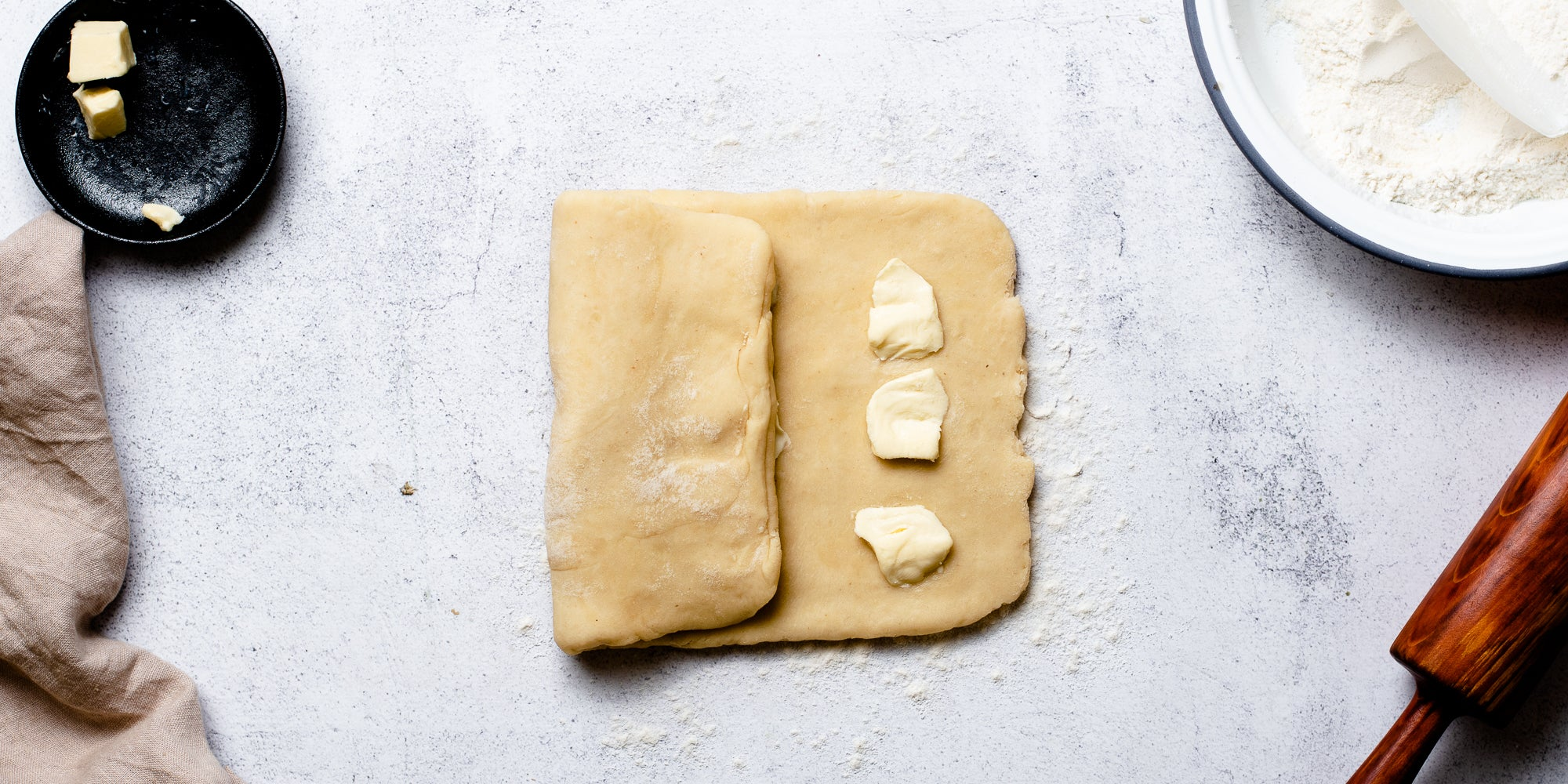 Puff Pastry rolled out with knobs of butter ready to fold into the dough. Next to a rolling pin, bowl of flour and dish of butter