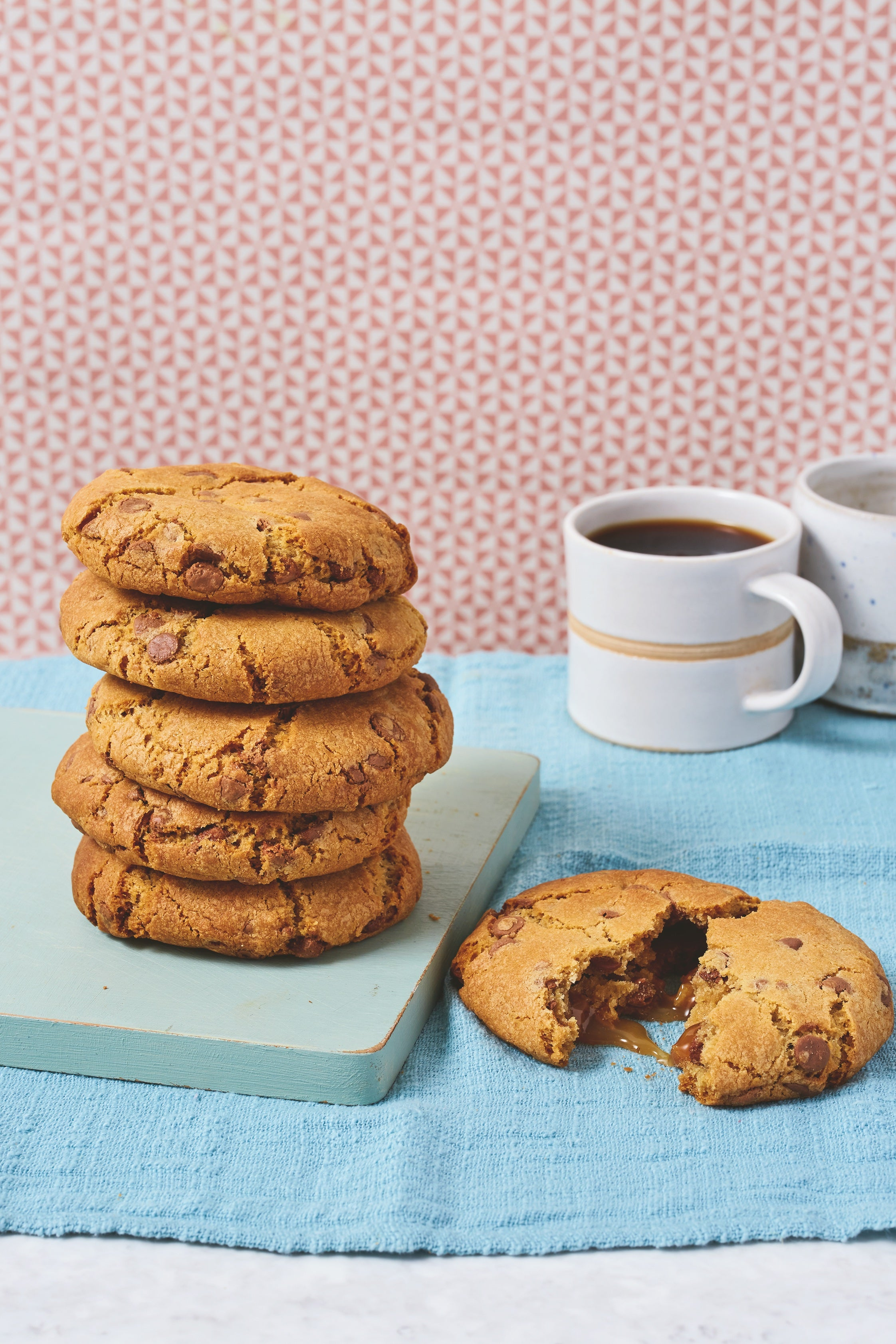 Stack of 5 cookies and one pulled open in front with caramel centre. Cup of coffee in background