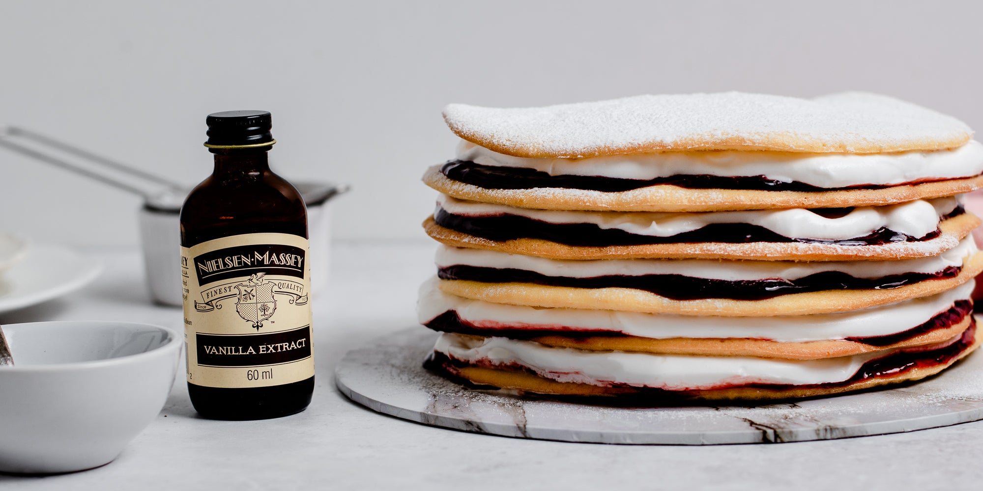 Close up of Danish Layer Cake stacked ontop of a marble serving plate, next to a bottle of Nielsen-Massey Vanilla Extract