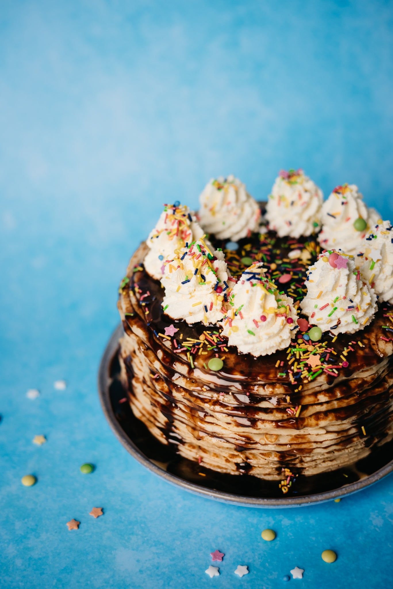 Tower of crepes in cake, covered in chocolate sauce, sprinkles and whipped cream