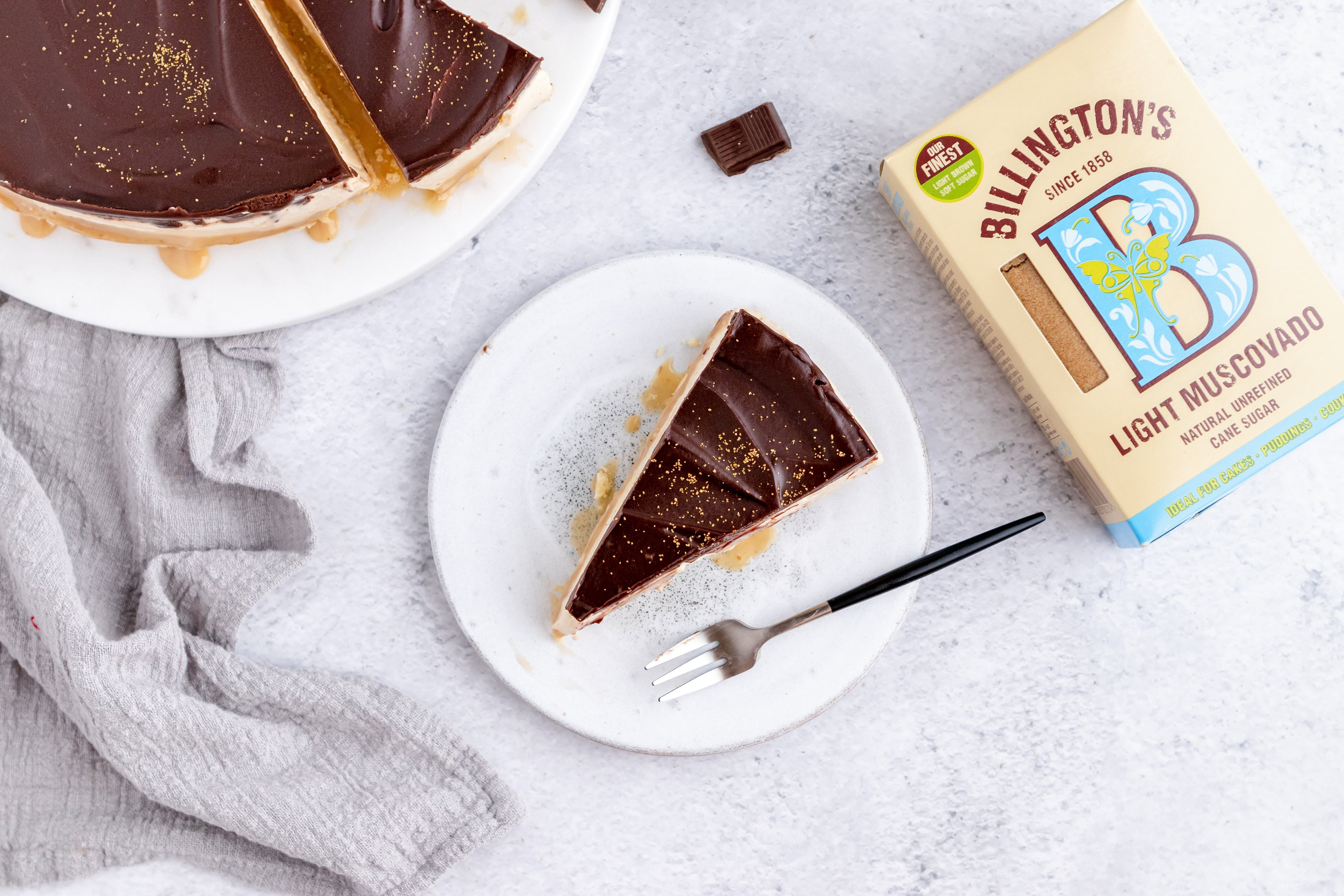 Millionaire's Cheesecake slice with a fork next to a box of Billington's Light Muscovado sugar