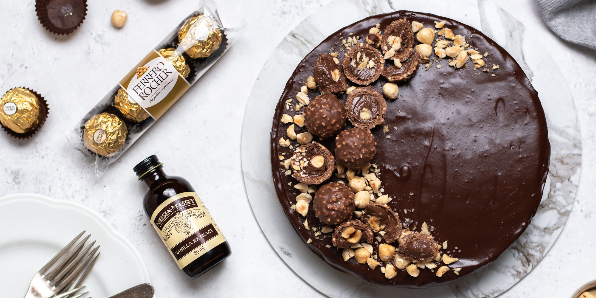 Top view of Gluten Free Chocolate Truffle Sachertorte sprinkled with hazelnuts, next to a packet of Ferrero Rocher's and a bottle of Nielsen-Massey Vanilla Extract