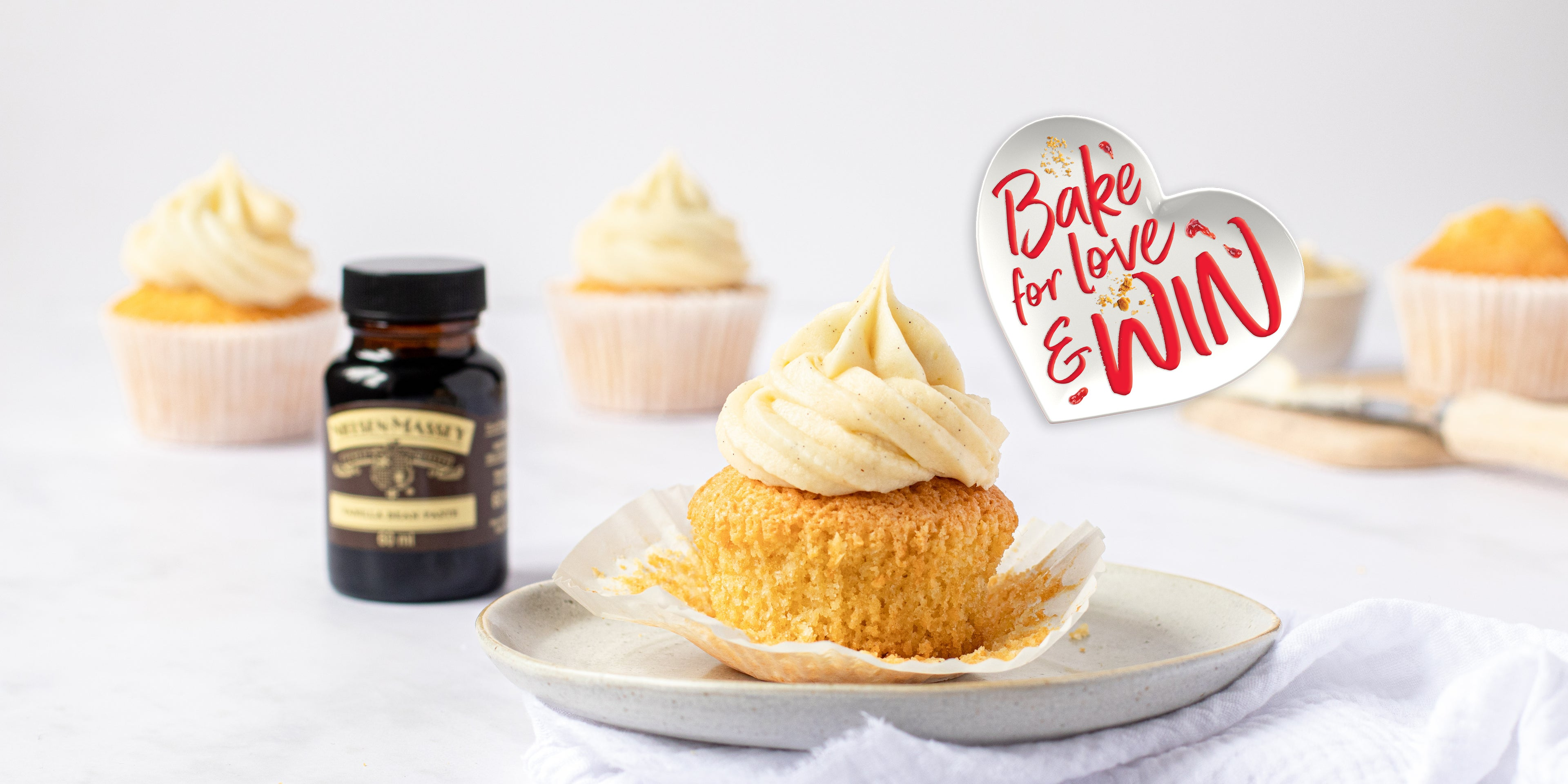 Close up shot of a vanilla cupcake next to a small jar of Neilsen Massey's vanilla extract