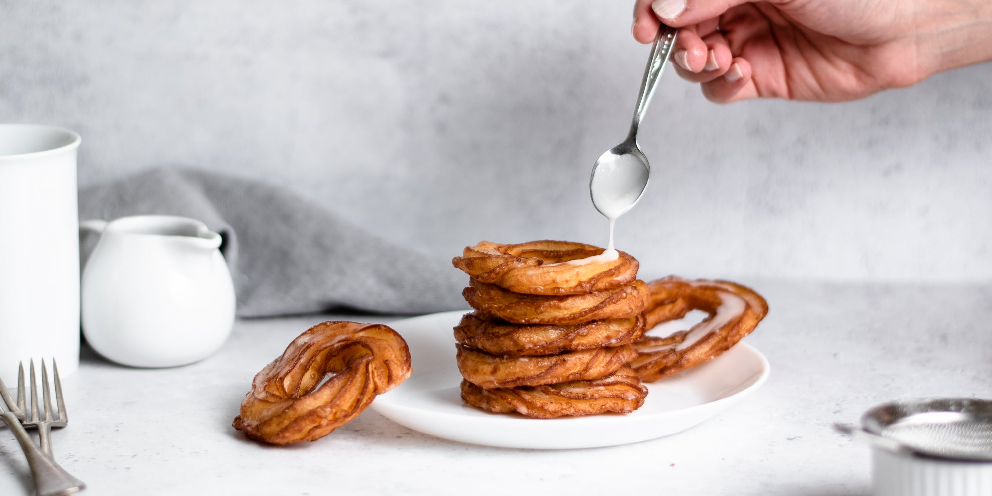 Stack of Apple Cider Crullers being drizzled with Icing with a hand holding a spoon
