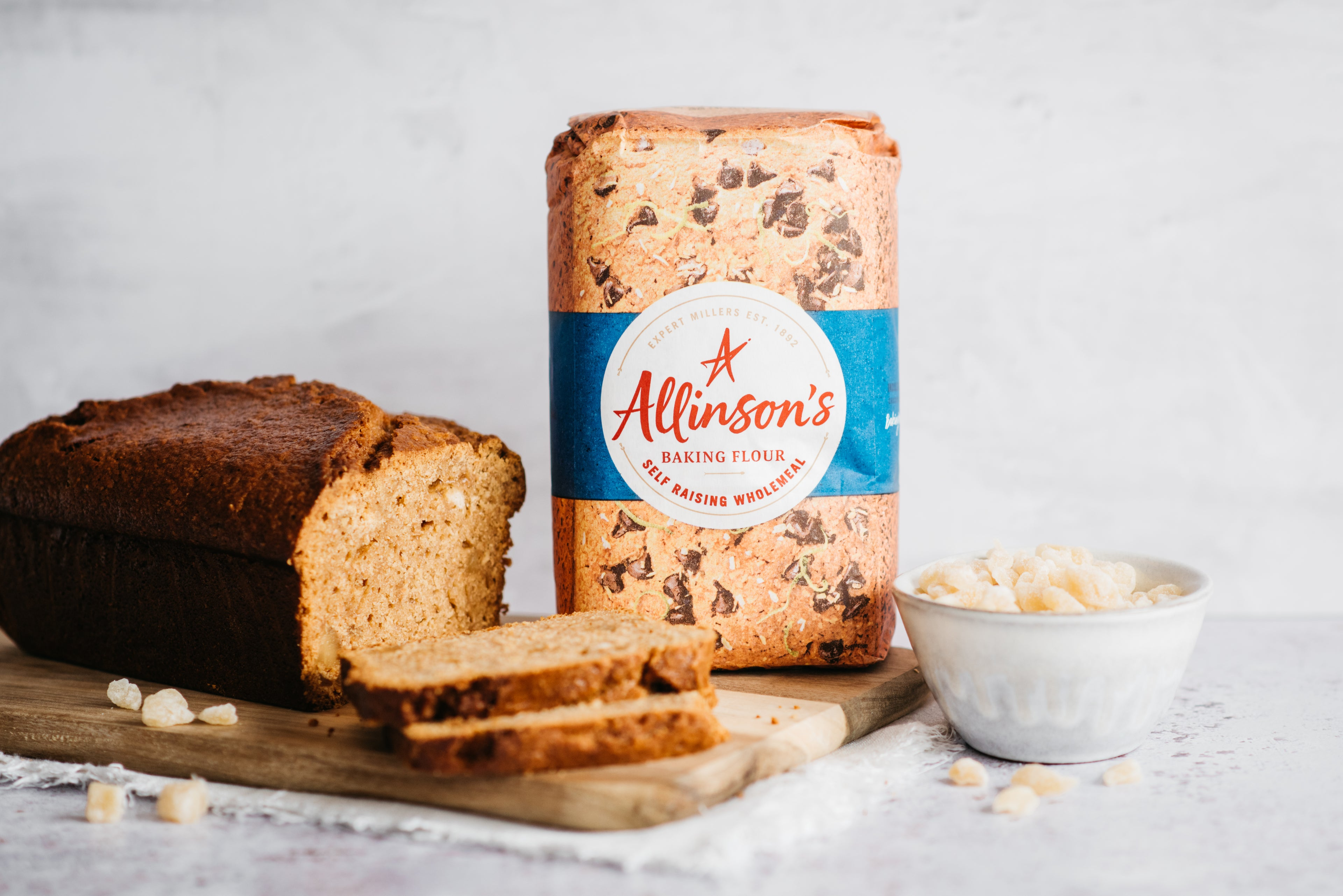 Gingerbread Loaf sliced on a wooden serving board, next to a bag of Allinson's self raising flour and a bowl of crystallised ginger
