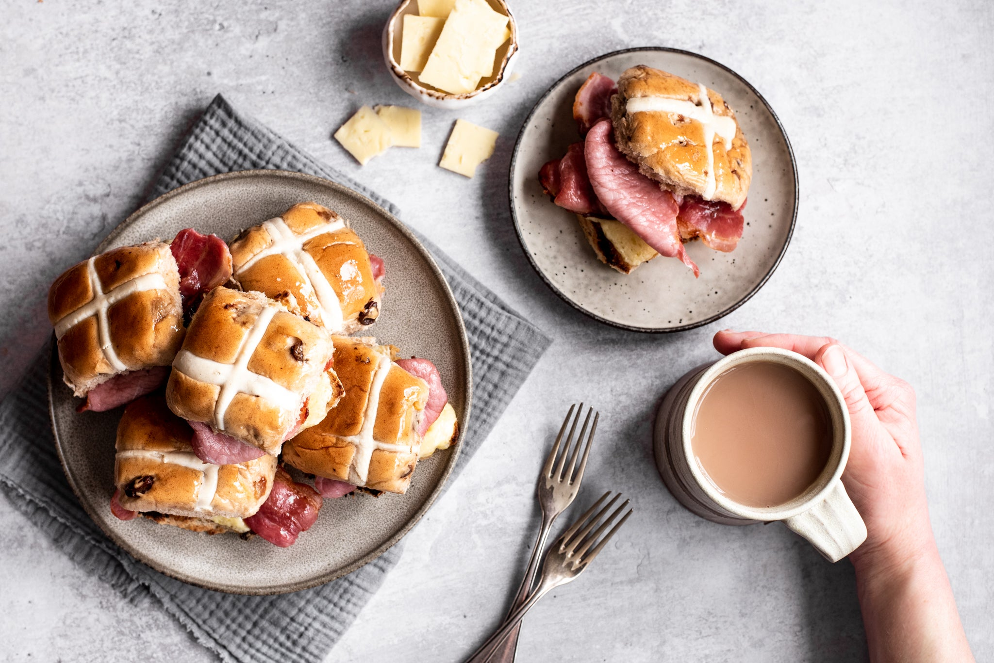 Plate of hot cross buns stacked on top of each other. Plate with hot cross bun and bacon. Cup of tea and hand. Two forks
