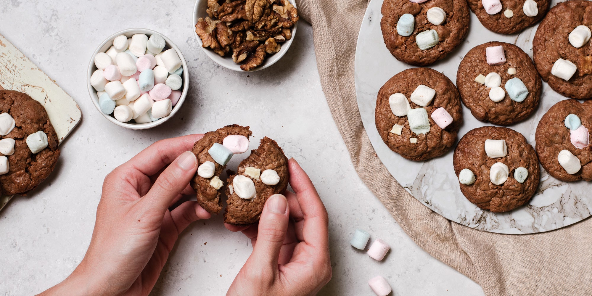 Rocky Road Cookies with hands opening a cookie to show the gooey insides