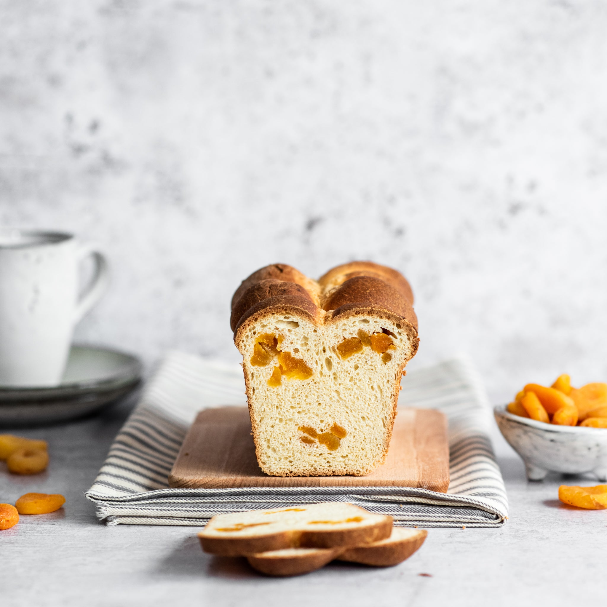 Brioche loaf with two slices cut in front, cup in background and pot of apricots