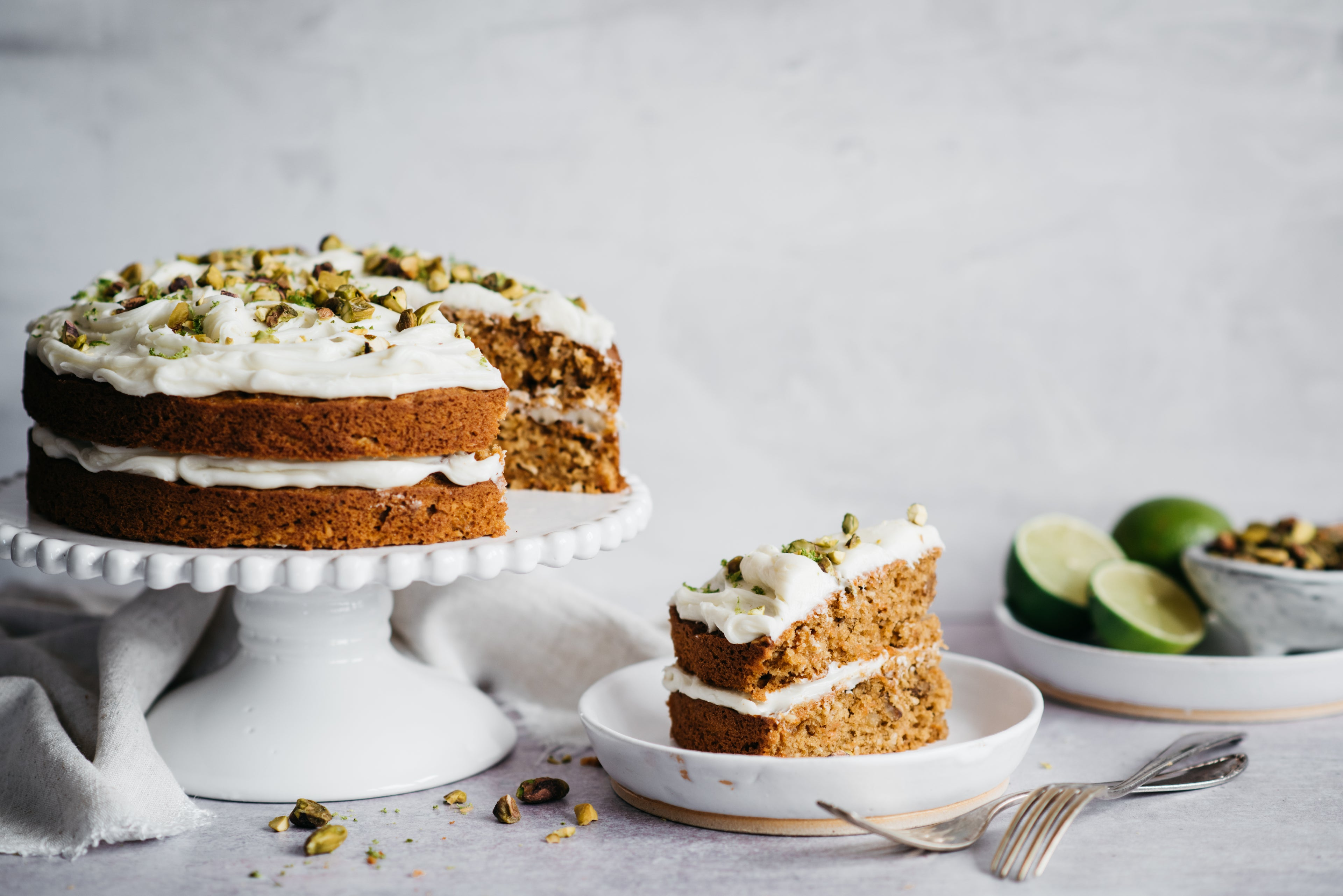 Carrot cake with icing on cake stand and cake slice on plate. Limes in the background