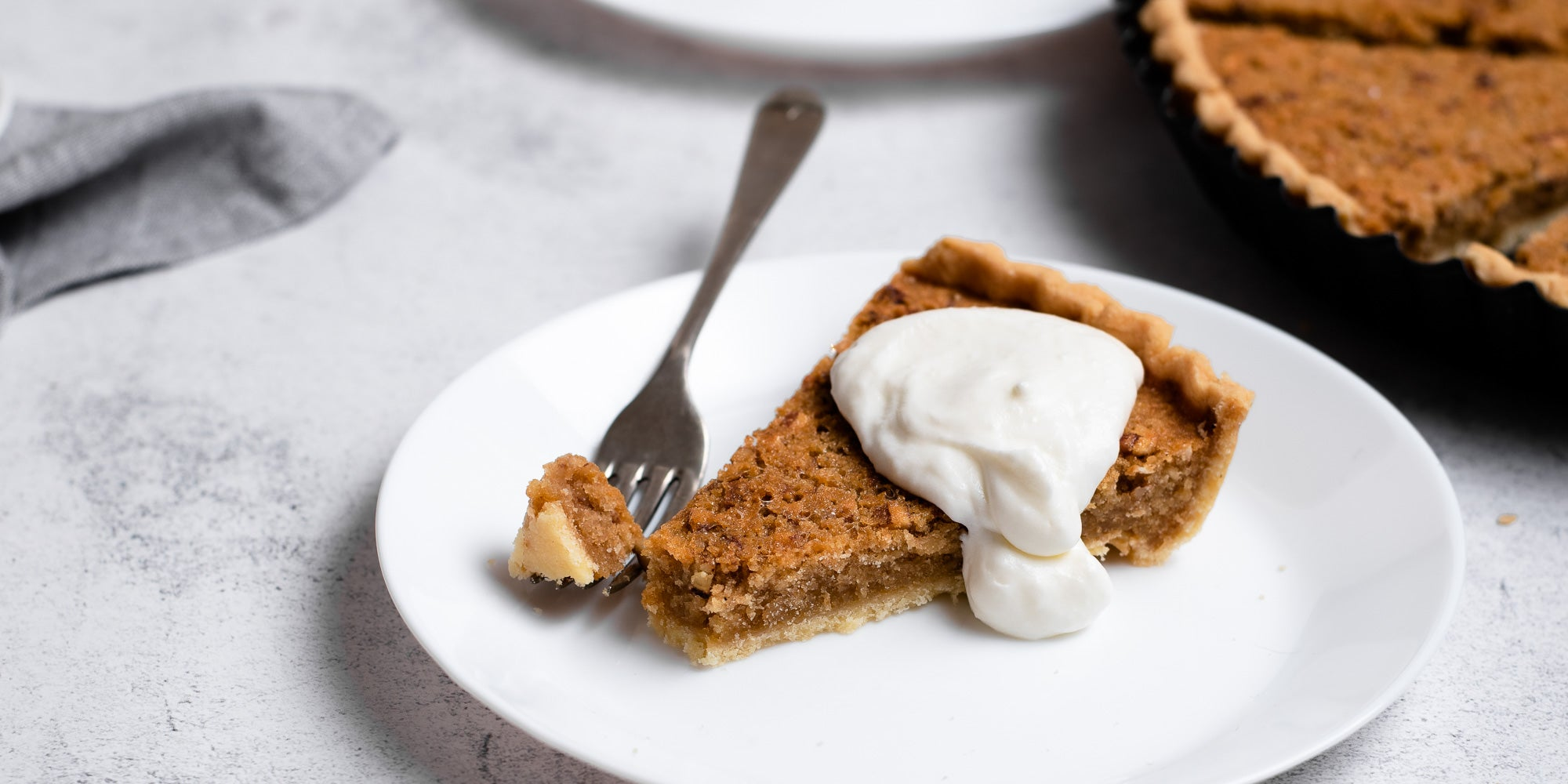 Treacle Tart on a plate with fork and dollop of cream