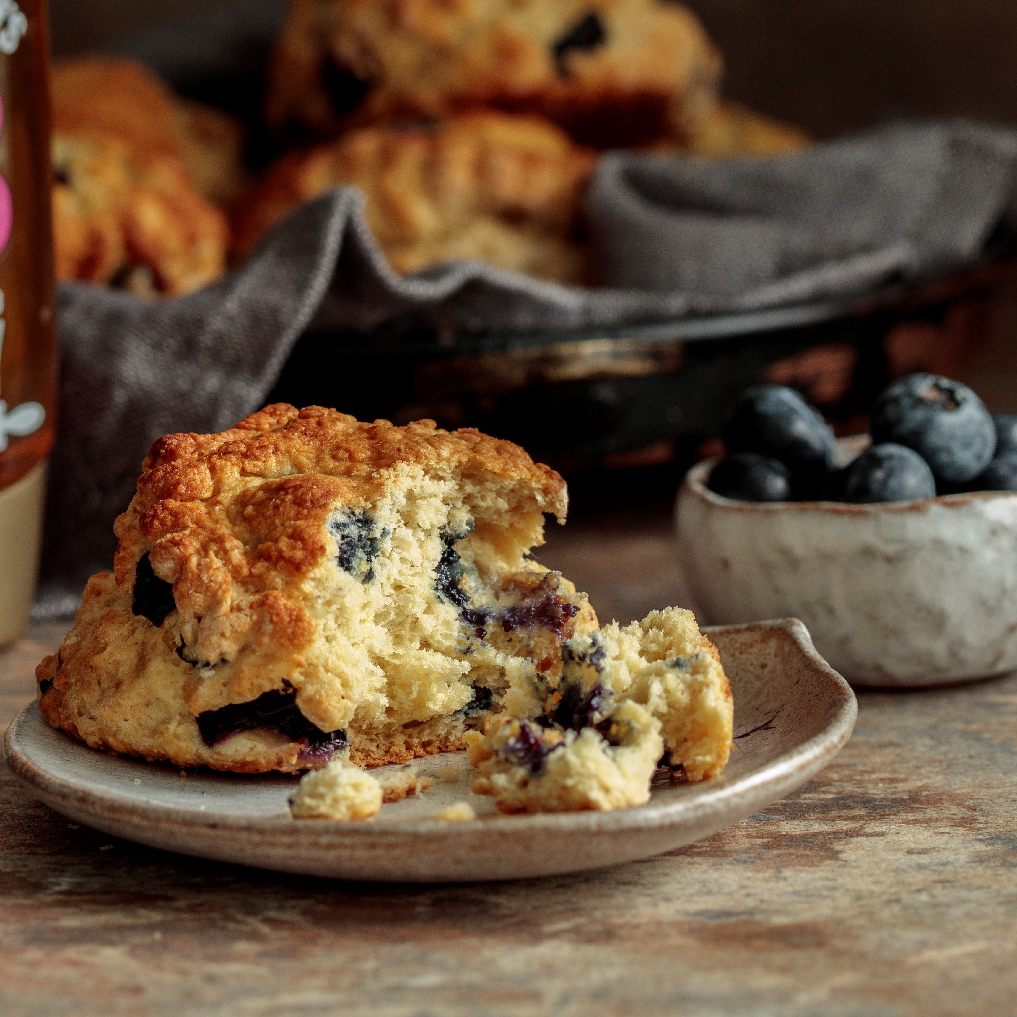 Blueberry honey scone on plate torn open with bowl of blueberries