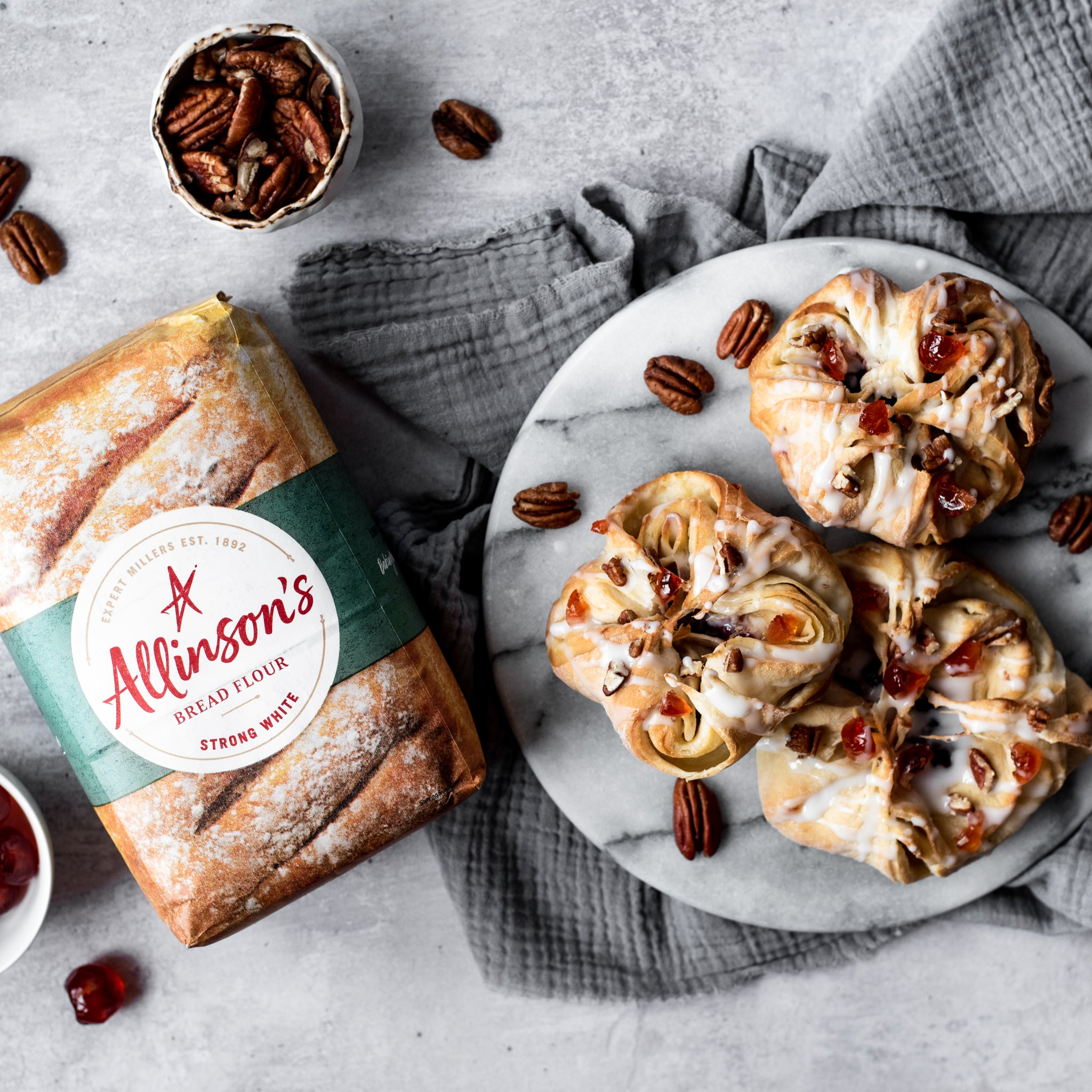Overhead shot of 3 danish pastries on a plate with pecan nuts and flour pack