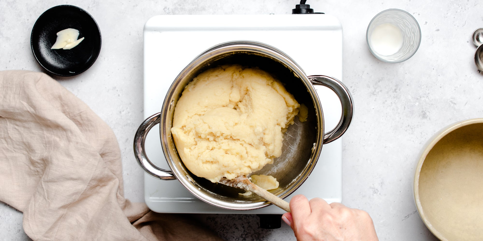 Top view of choux pastry being mixed together in a pan, ready to pipe for Chouxnuts