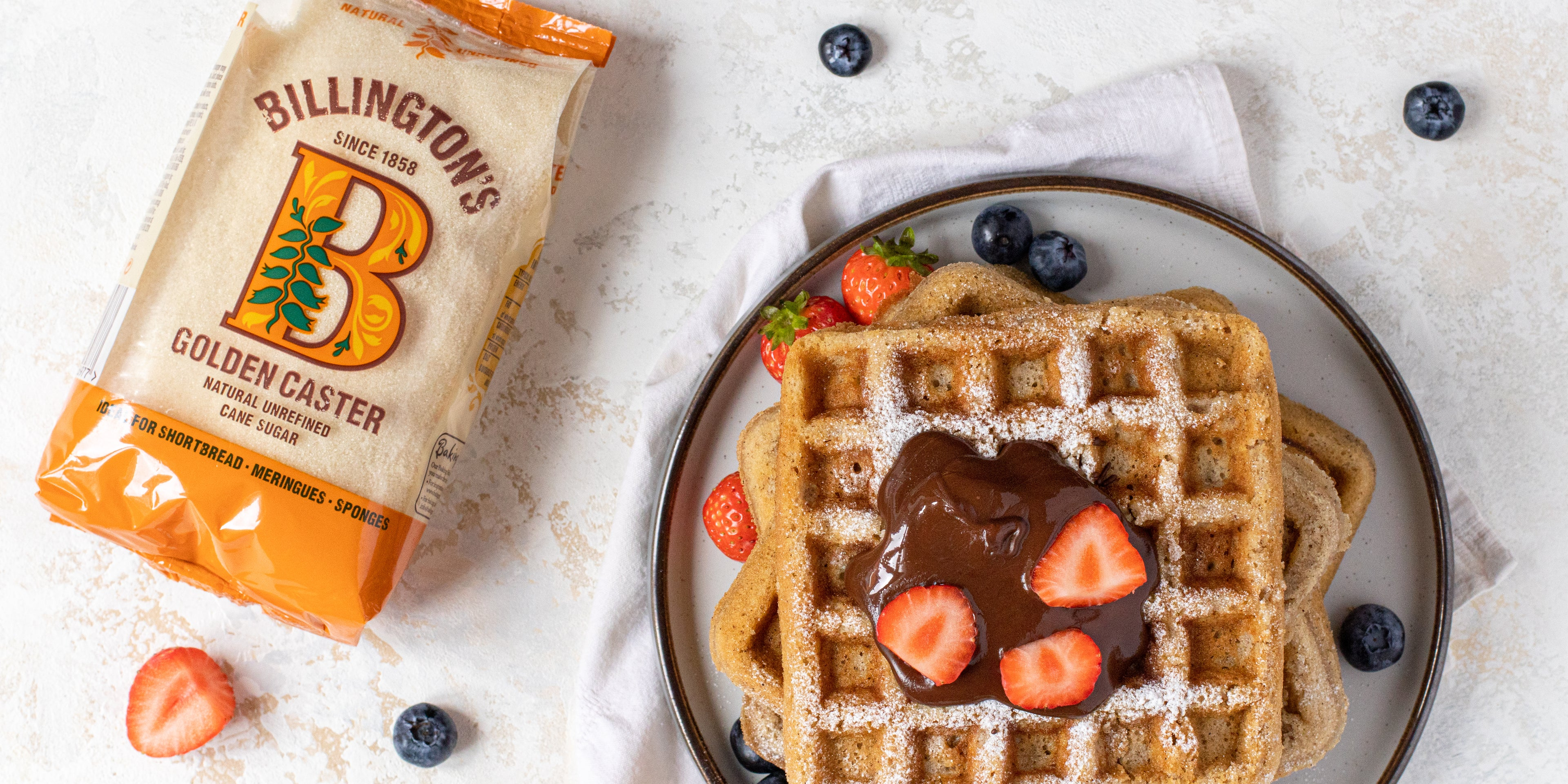 Stack of Waffles topped with chocolate and strawberries, next to a bag of Billington's Golden Caster sugar