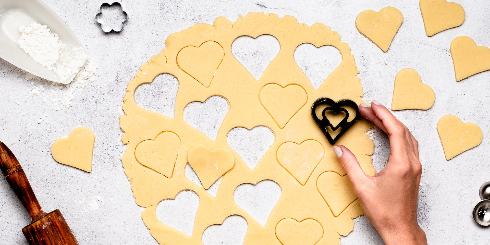 Top down view of a hand using a heart-shaped cookie cutter to cut out gluten free biscuit dough