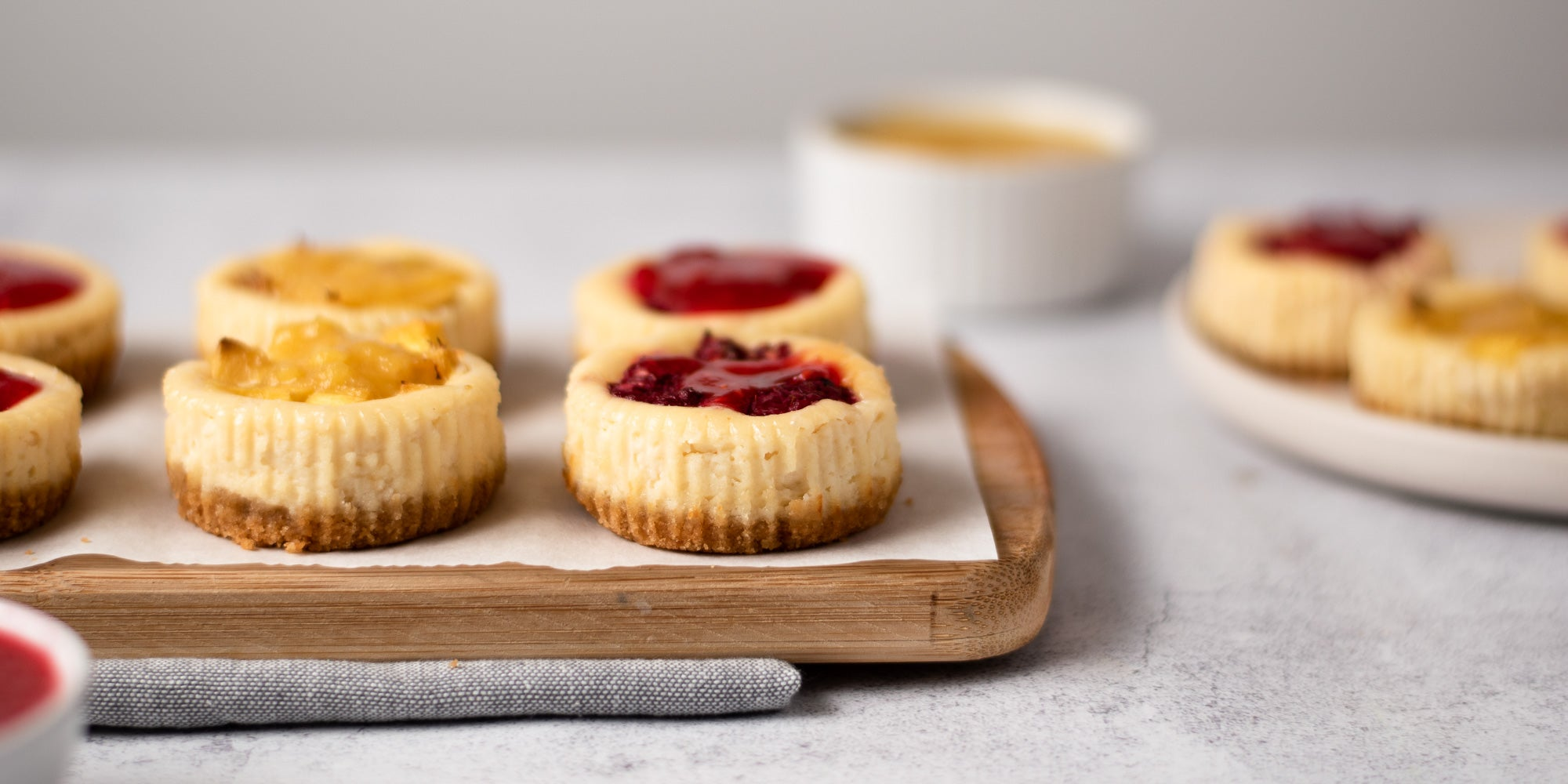 Mini cheesecakes topped with fruit on a wooden board